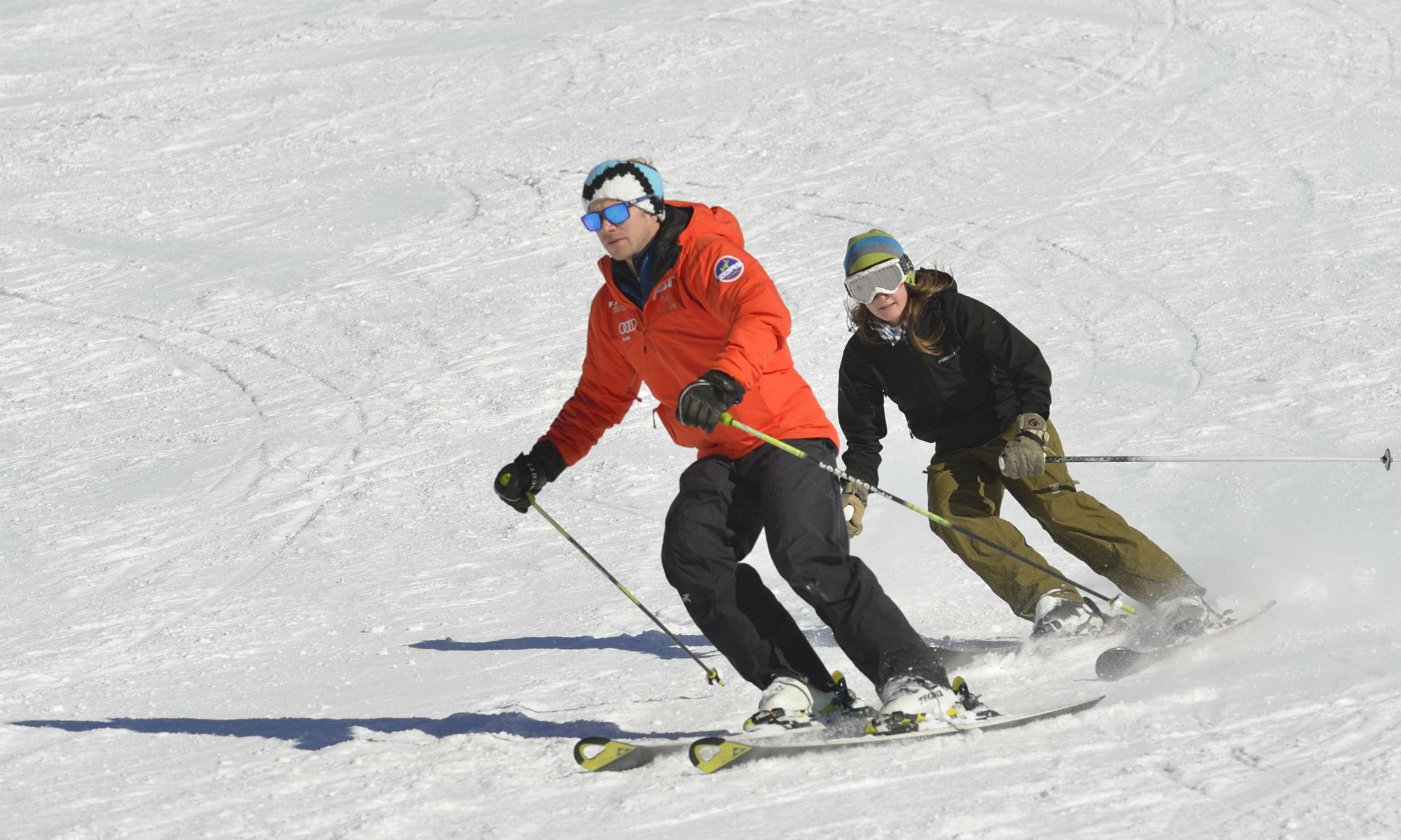 Zwei Skifahrer beim Üben der Skitechnik auf der Piste