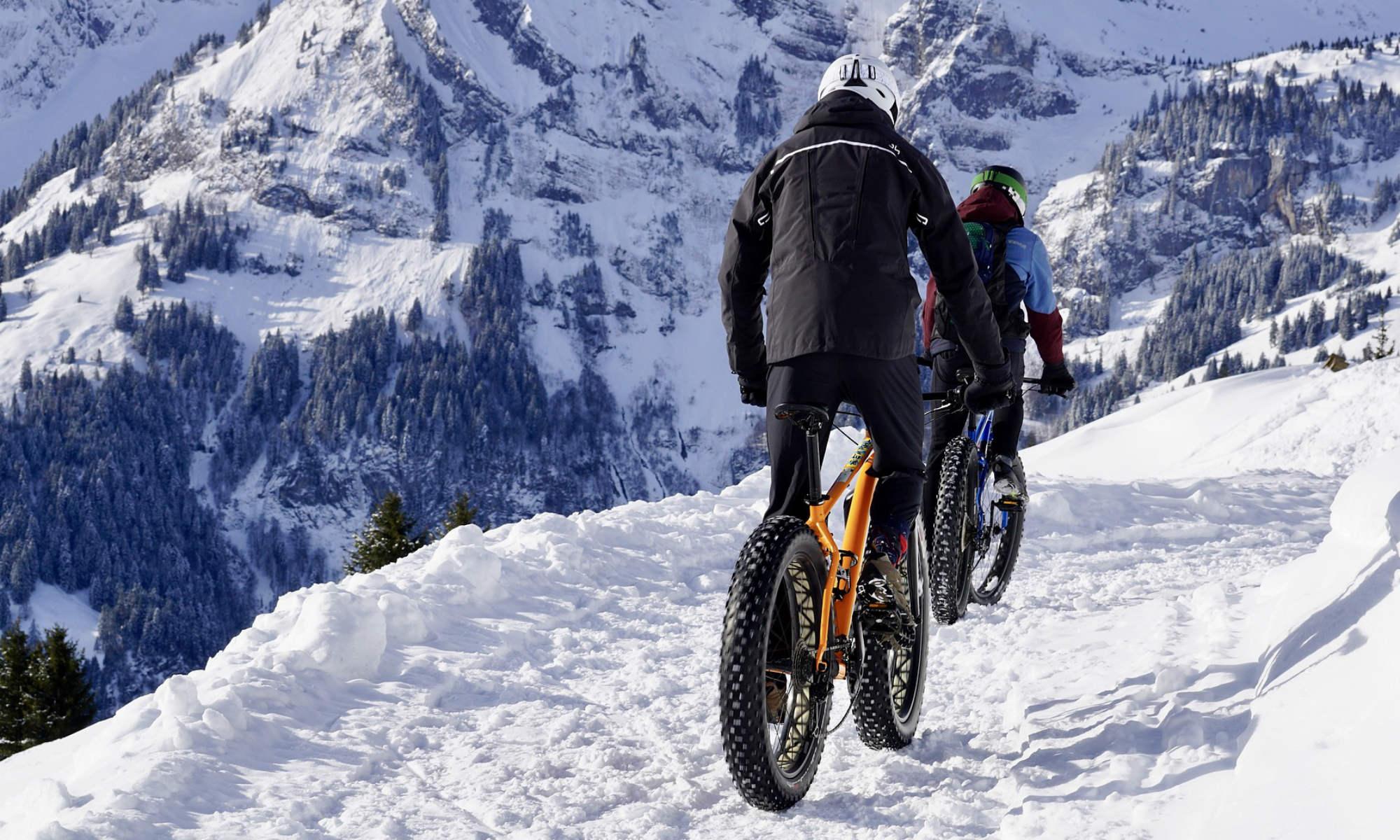 2 Radfahrer mit Fatbikes fahren durch den Schnee, im Hintergrund verschneite Berge.