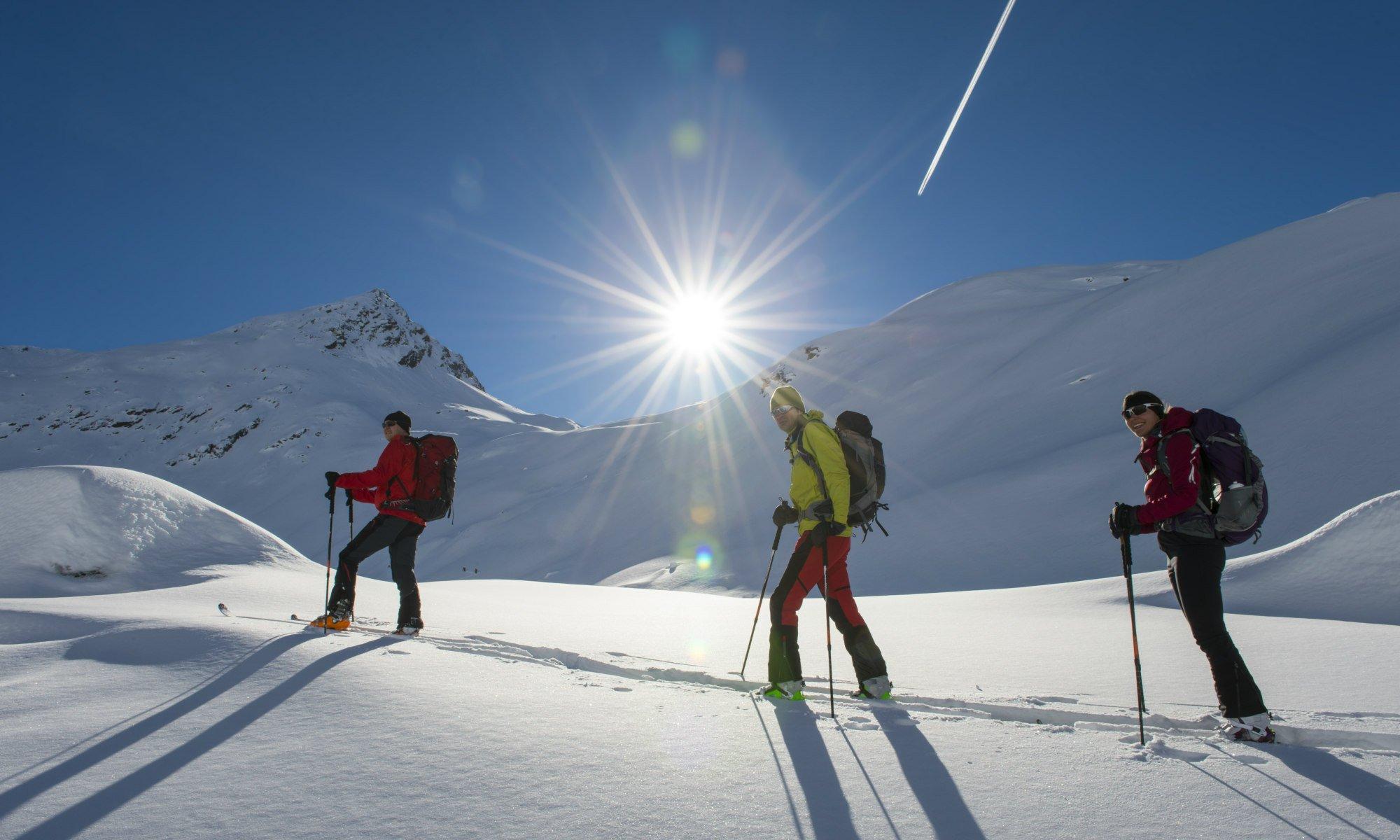3 Personen bei einer Skitour durch die verschneite Berglandschaft.