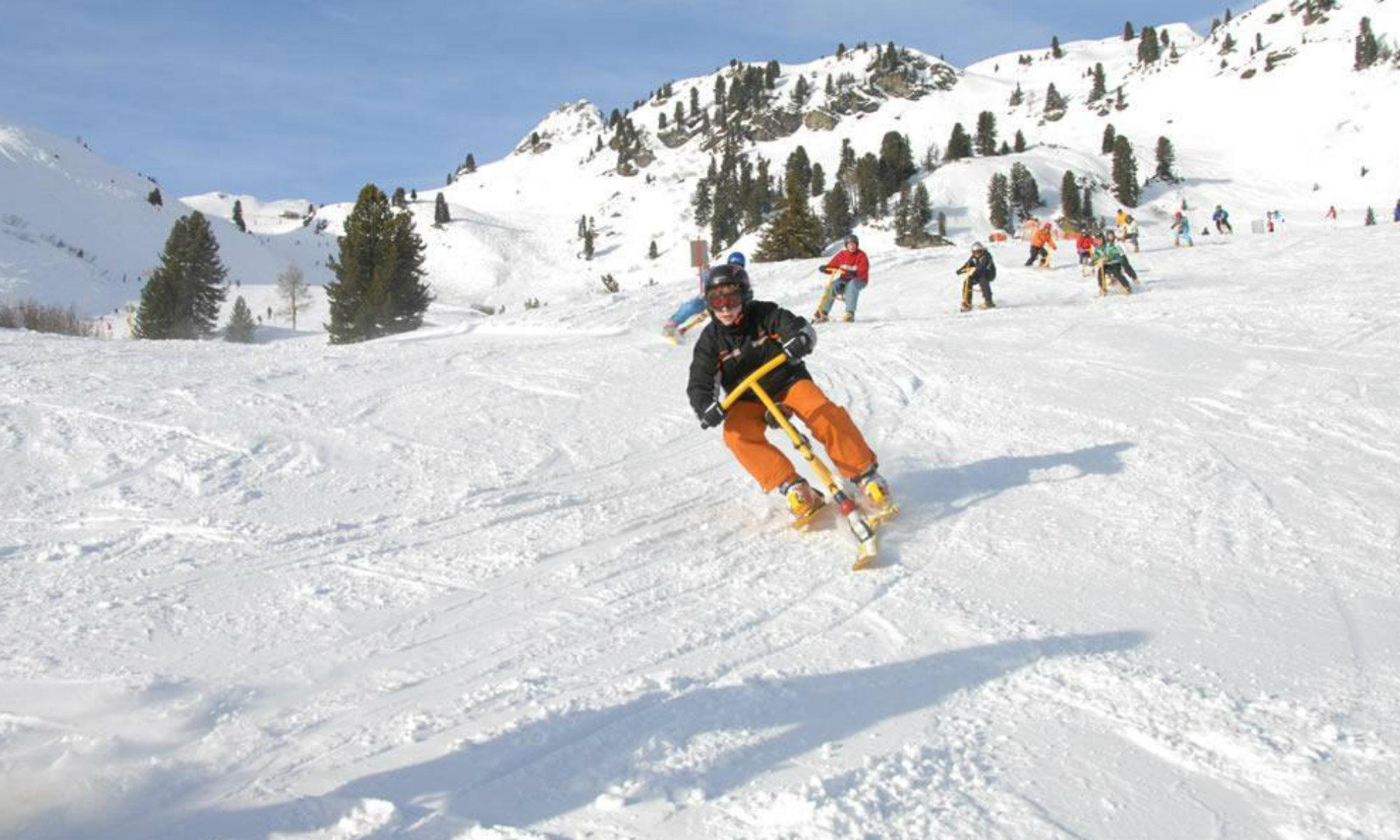Mehrere Personen machen mit Snowbikes Kurven auf der Piste.