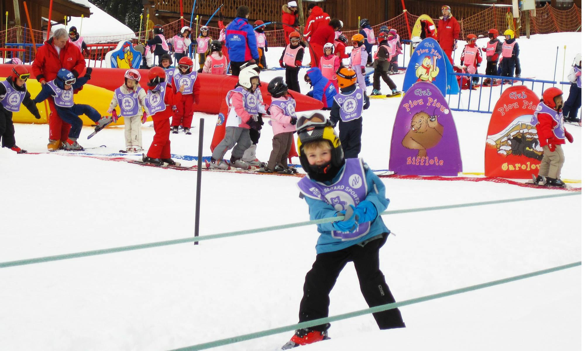 Un petit skieur souriant utilise une télécorde dans un jardin des neiges.