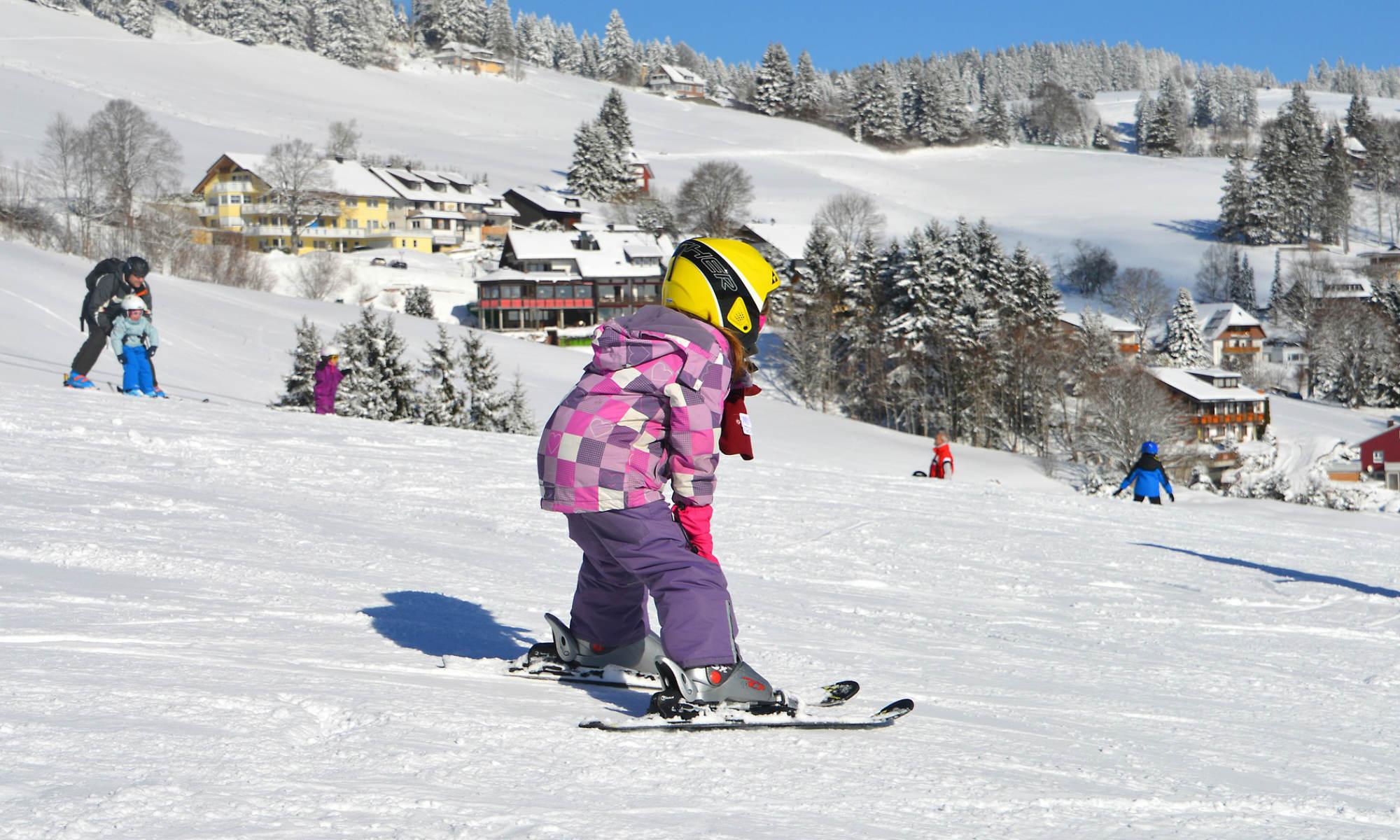 Une petite skieuse descend une piste de ski.