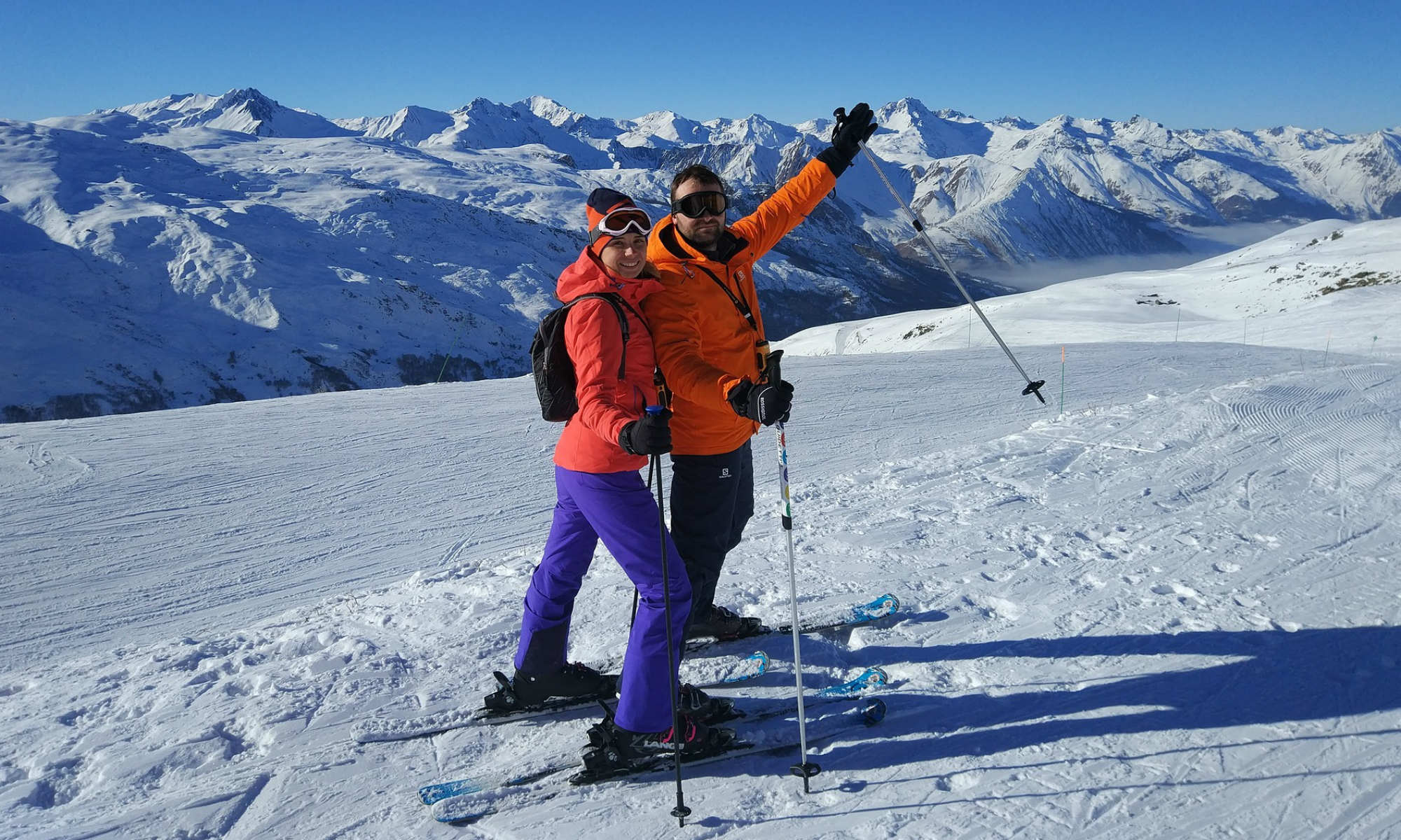 Deux skieurs souriants sur une piste ensoleillée.