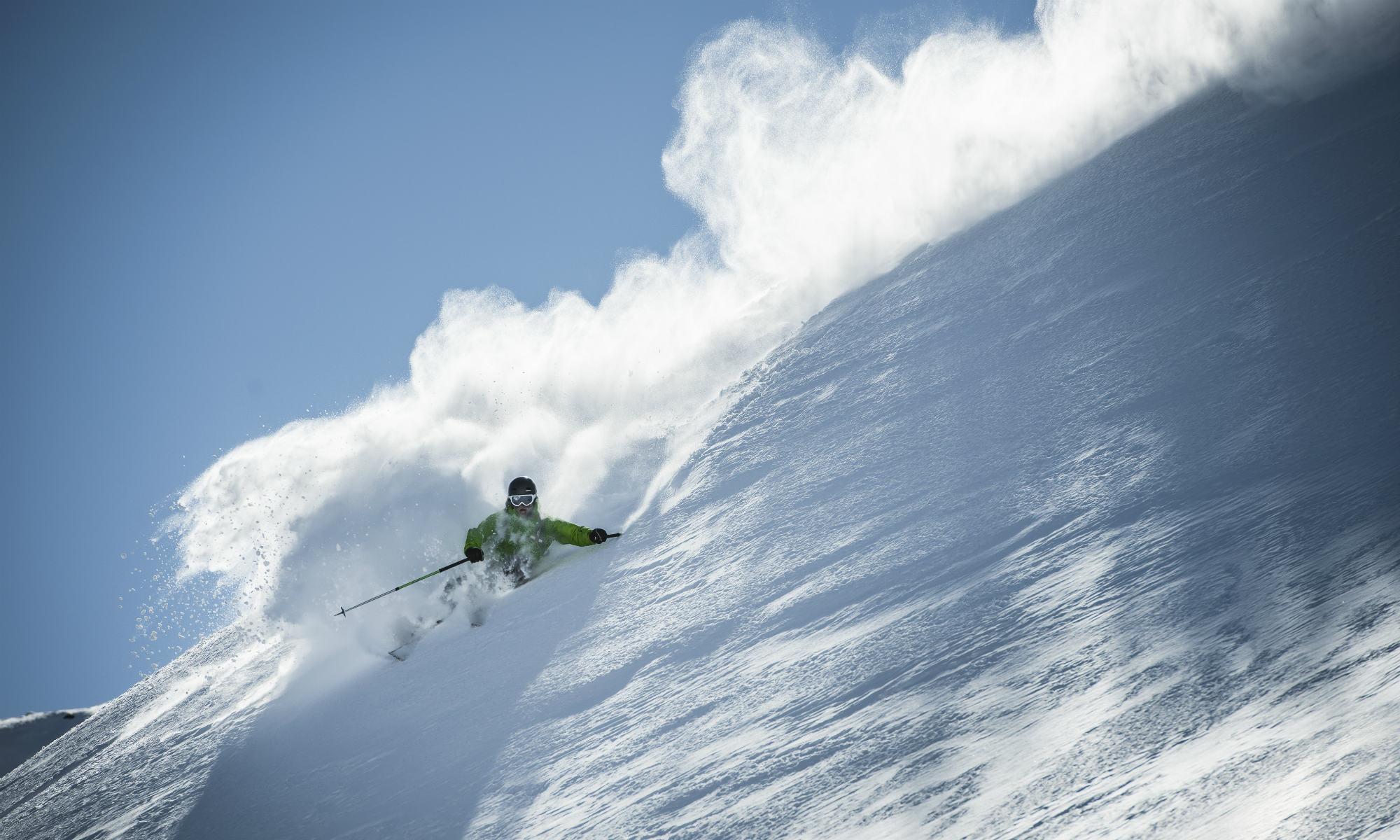 Un freerider che scia sulla neve fresca con bel tempo.