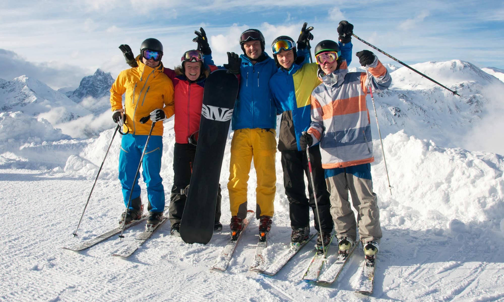 Une monitrice de ski et ses élèves lors d'un cours de ski pour adolescents sur une piste ensoleillée.