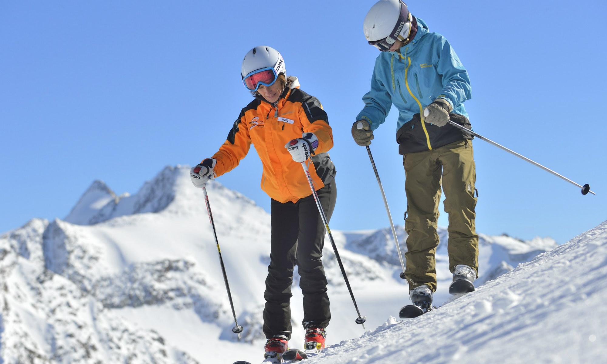 Deux skieurs sur une piste ensoleillée.