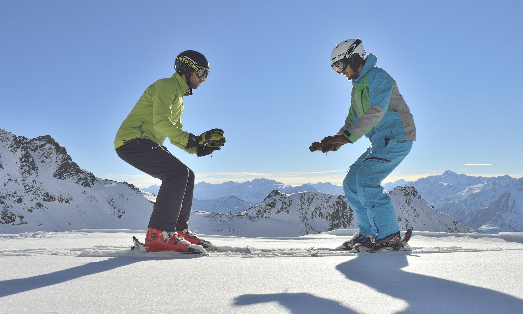 Deux skieurs effectuent des flexions des genoux pour s'échauffer.