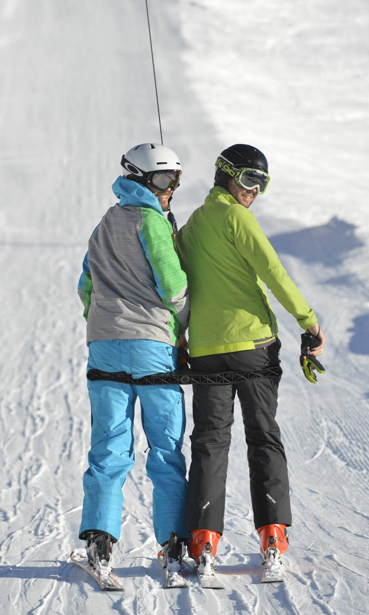 """Deux skieurs souriants sur un téléski en """"archet""""."""