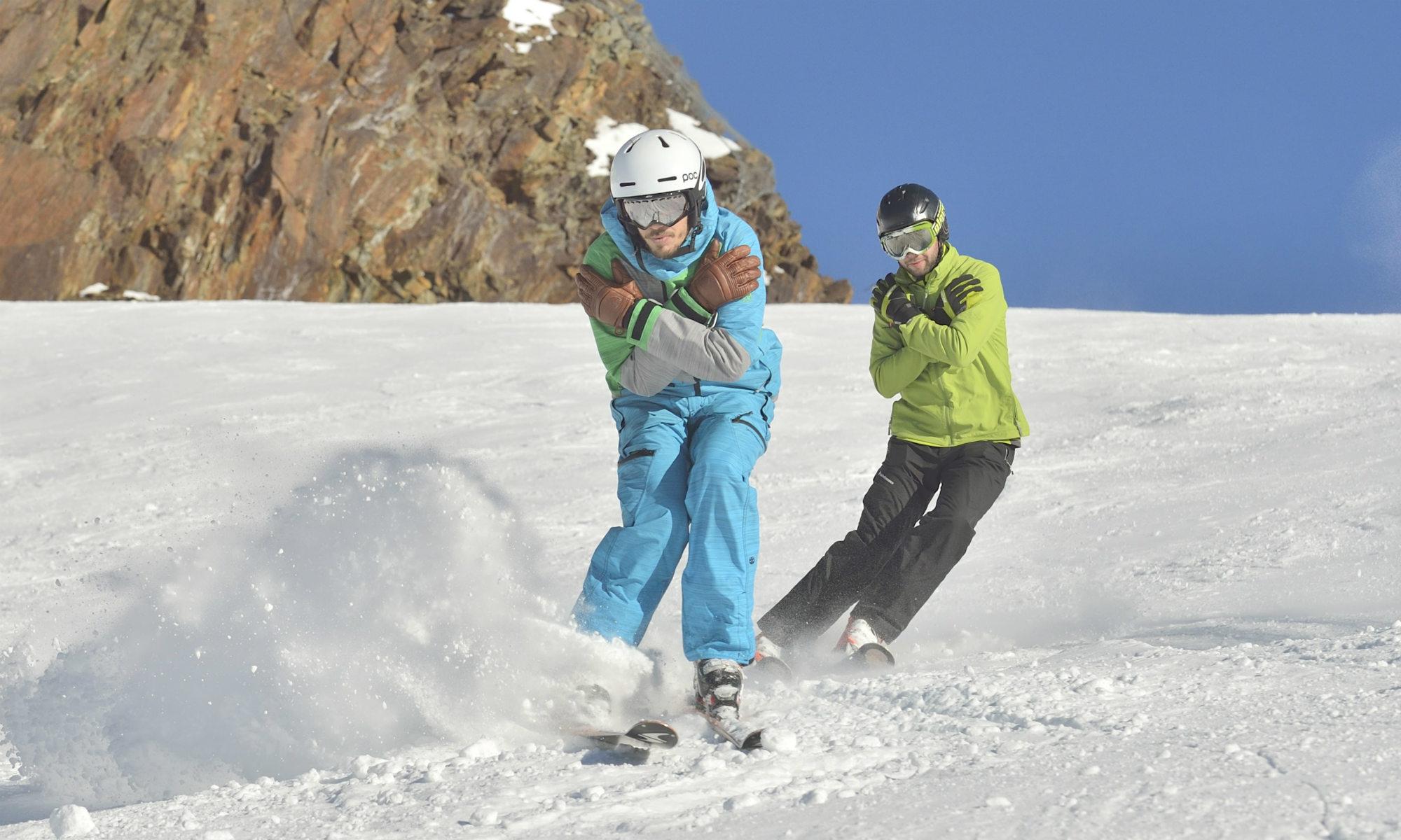 Deux personnes sur une piste de ski ensoleillée font des exercices techniques.