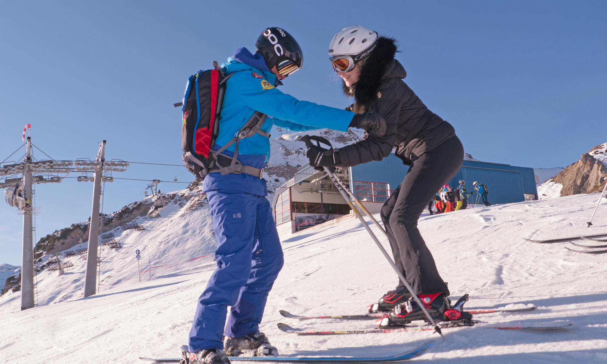 A skiing instructor helping a beginner find the right position.