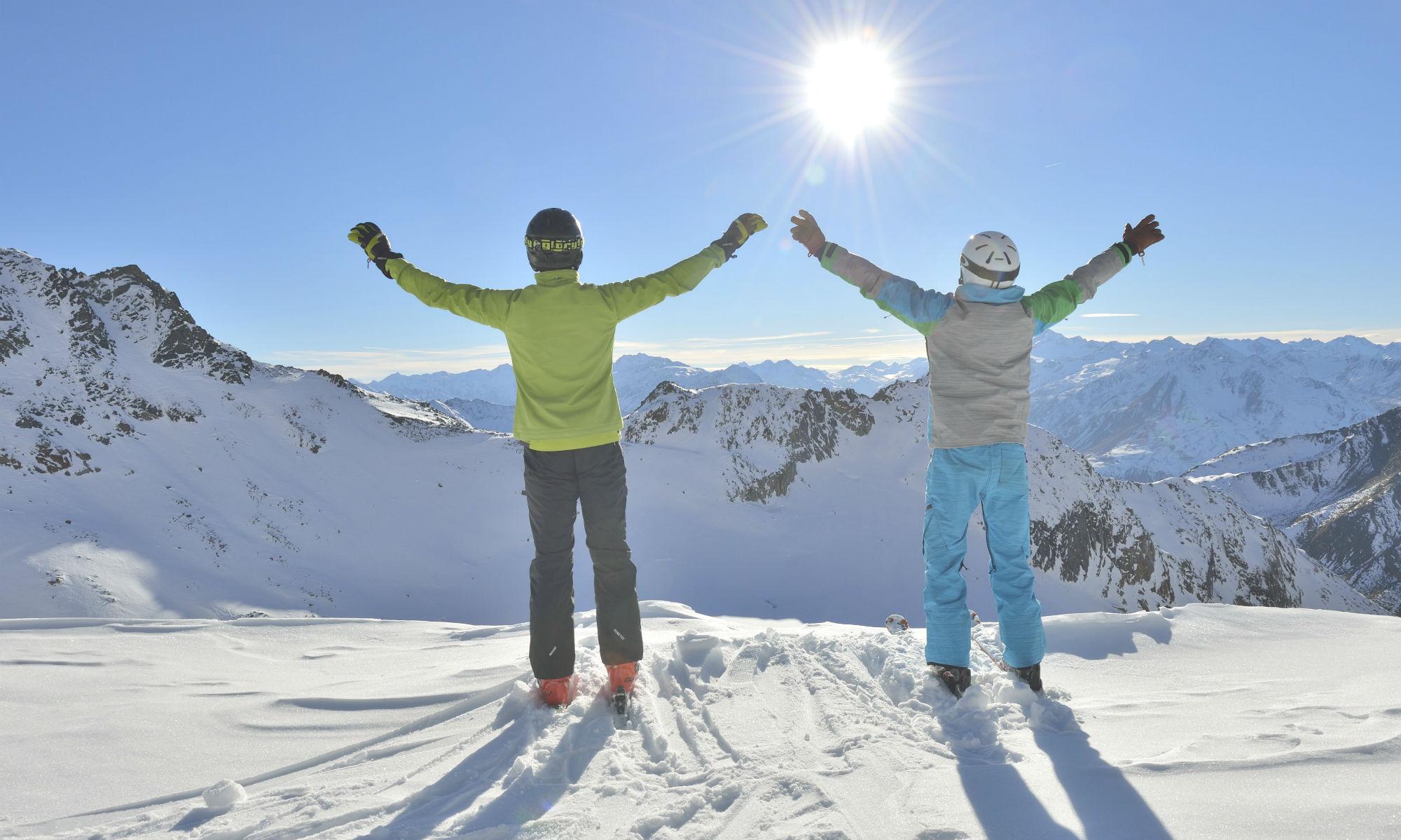 Deux skieurs profitent du soleil en haut d'une montagne.