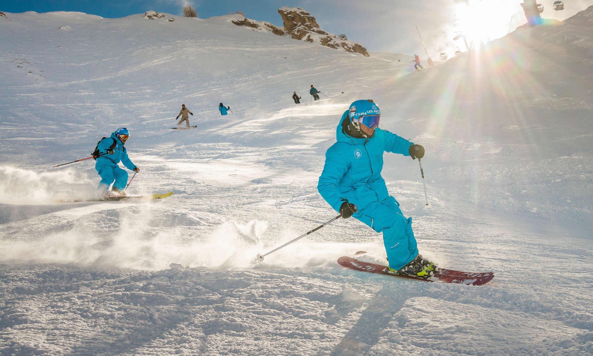 Des moniteurs de ski dans la neige poudreuse.