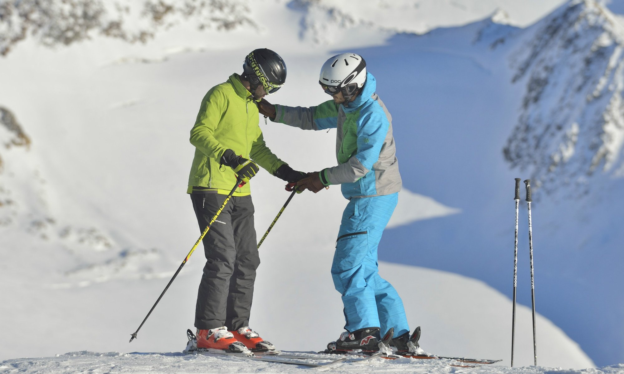 A ski instructor helping a participant to stand on the skis correctly.