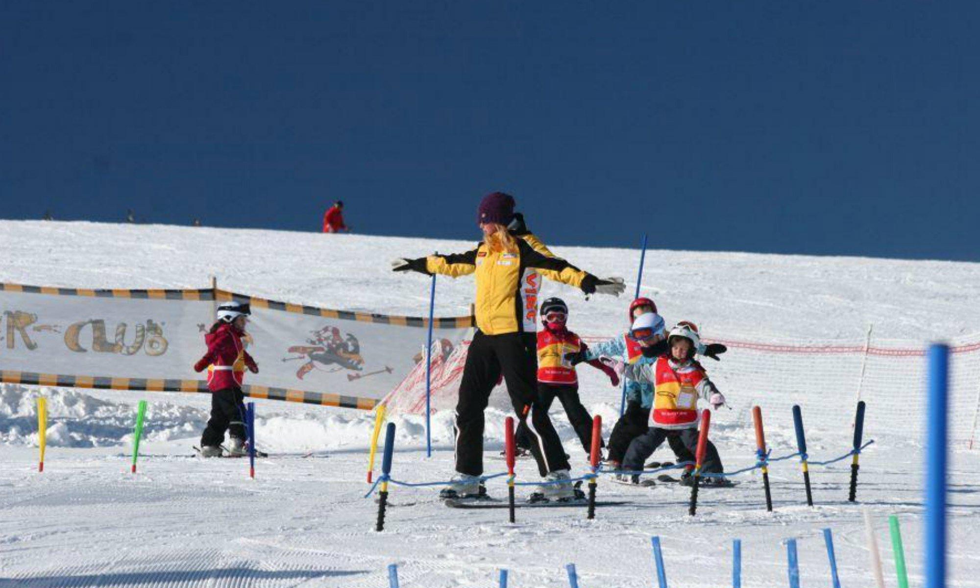 Eine Skilehrerin fährt mit einer Gruppe Kinder im Pflug durch das Kinderland.