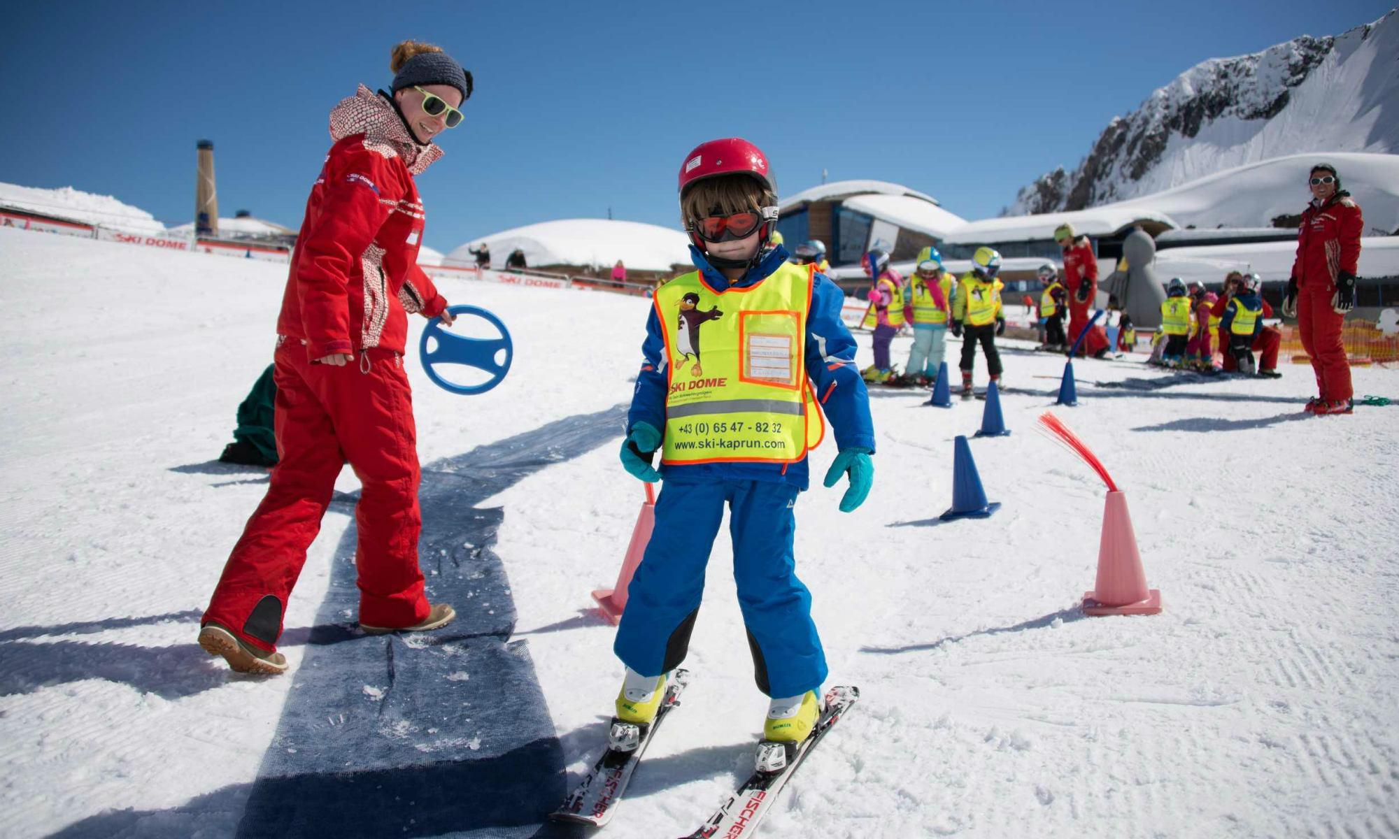 Ein Skilehrer und ein Kind üben das Skifahren im Kinderland in Kaprun.