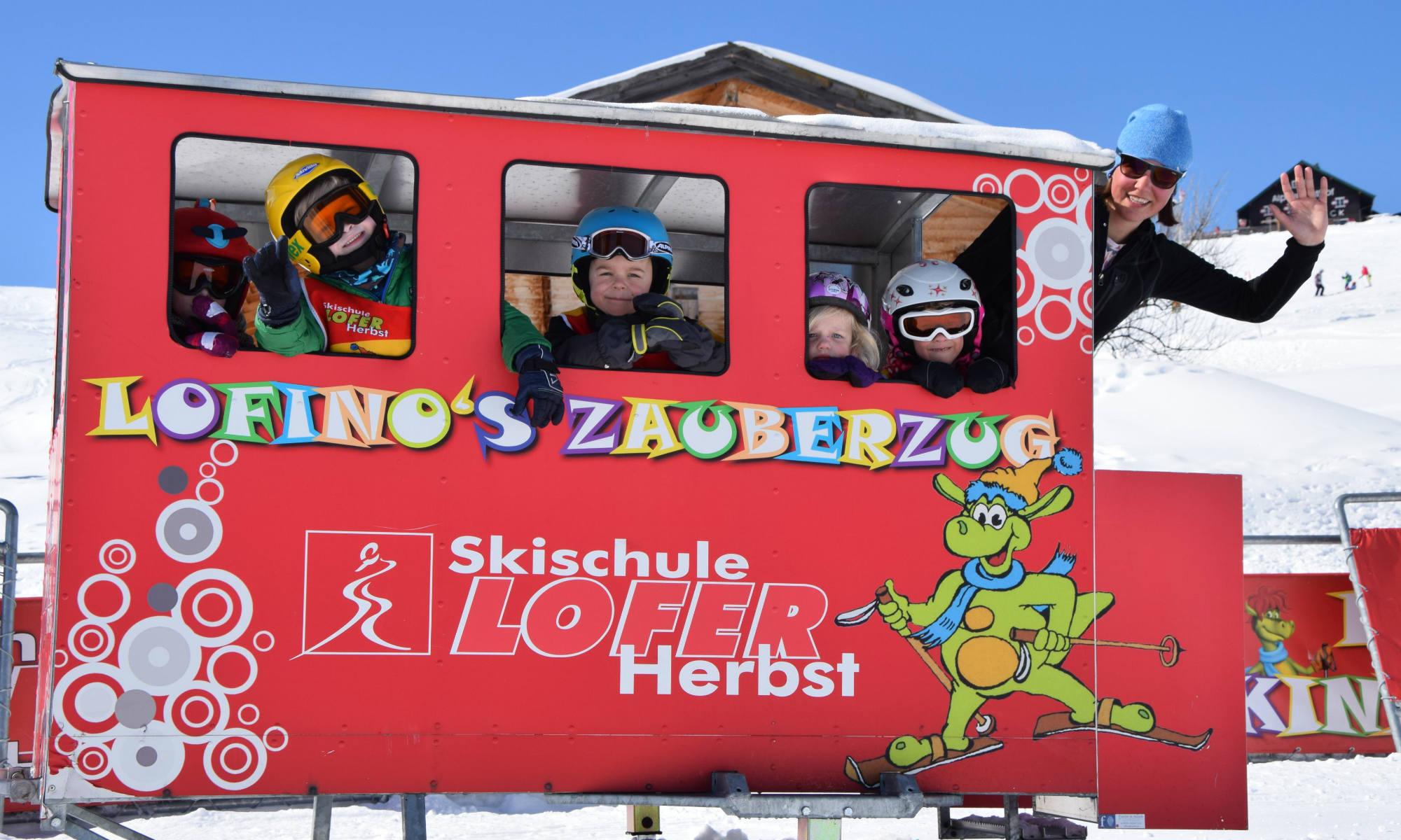 Eine Gruppe Kinder und eine Skilehrerin fahren mit dem Zauberzug zum Kinderland im Skigebiet Almenwelt Lofer.