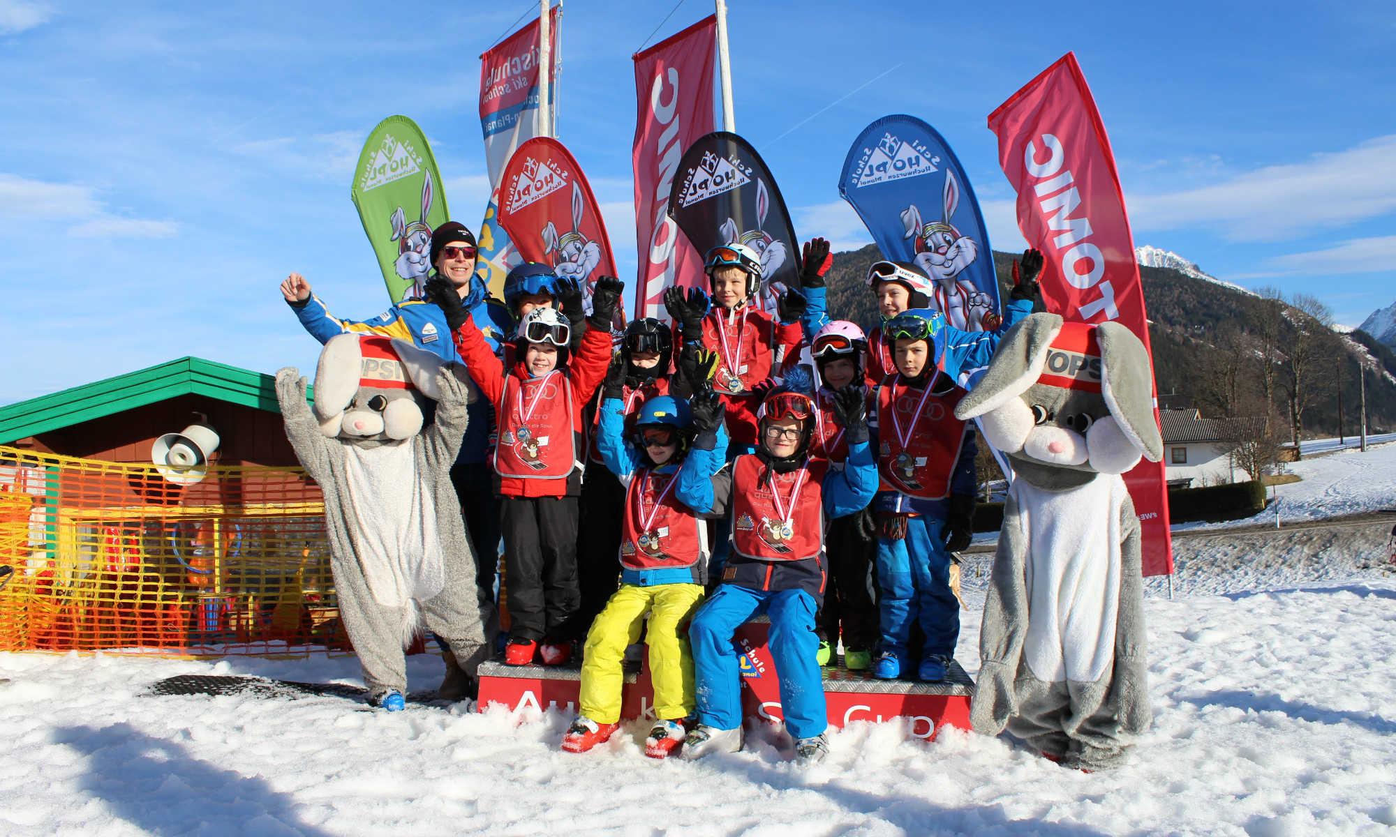 Eine Gruppe Kinder und das Maskottchen Hopsi freuen sich bei der Siegerehrung nach dem Skikurs in Schladming.