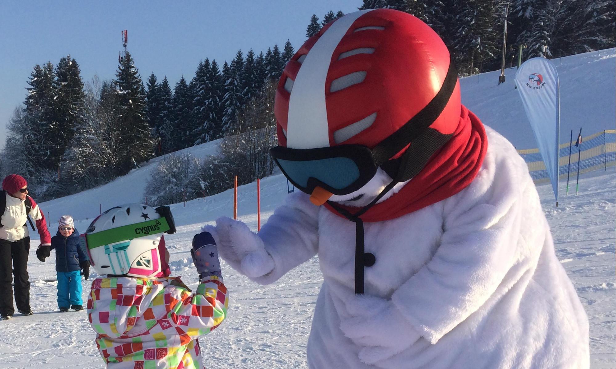 Das Maskottchen Valle klatscht mit einem Mädchen auf der Skipiste ein.