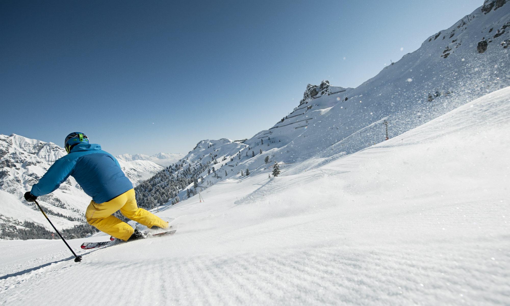 Ein Skifahrer fährt auf einer menschenleeren Piste.