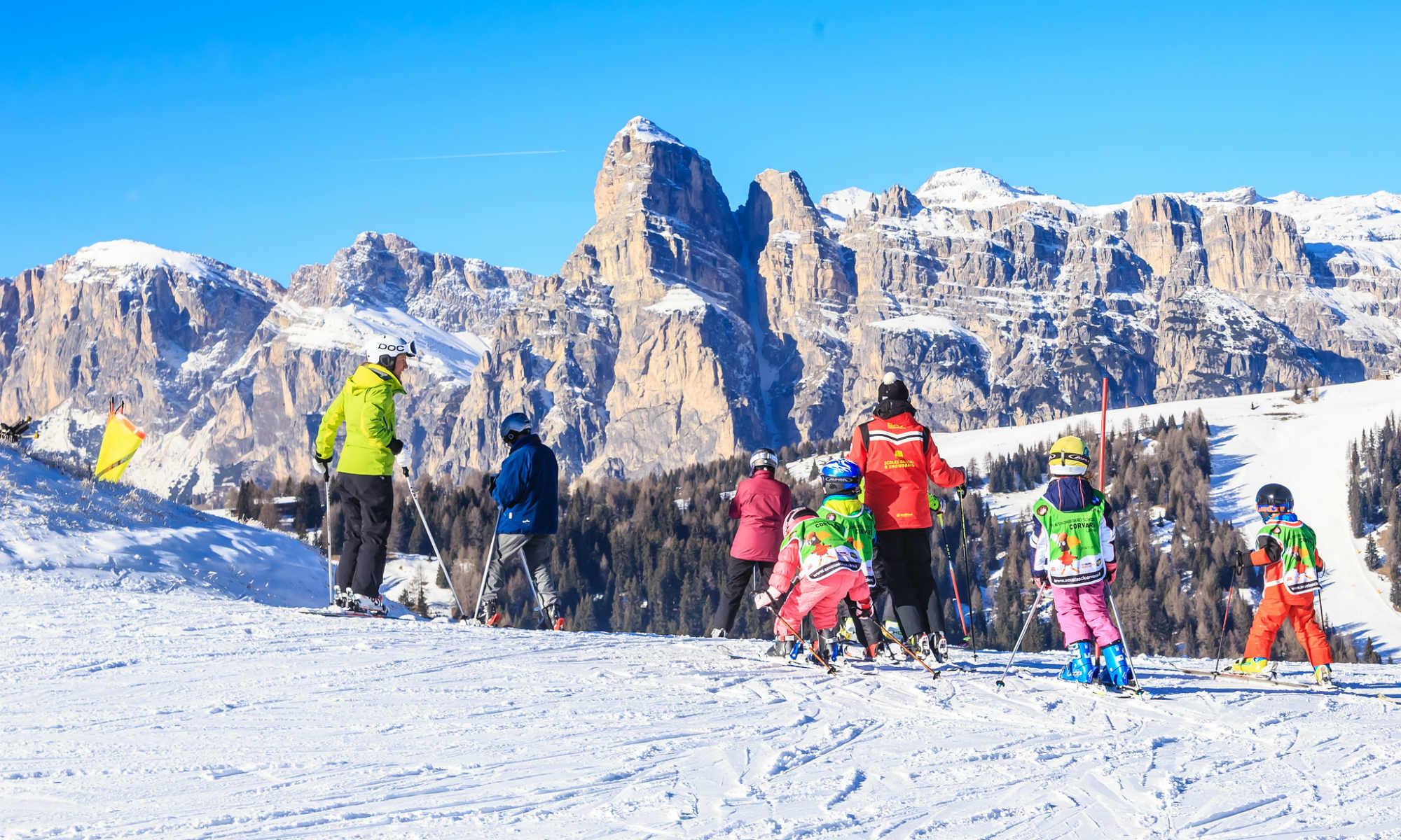 Kinder Skikurs vor der Kulisse der Dolomiten.