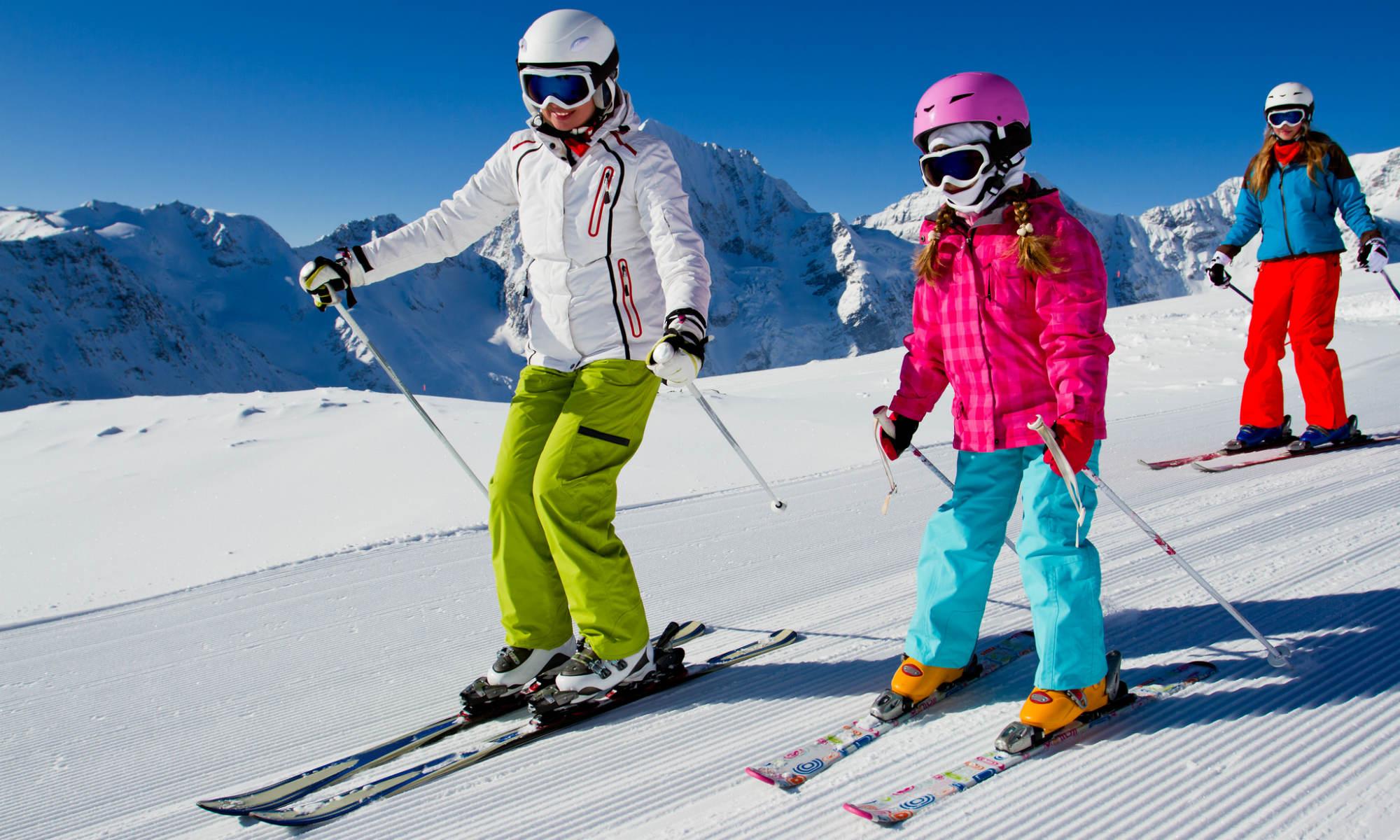 Familie beim Skifahren auf einer sonnigen Piste mit Bergpanorama im Hintergrund.