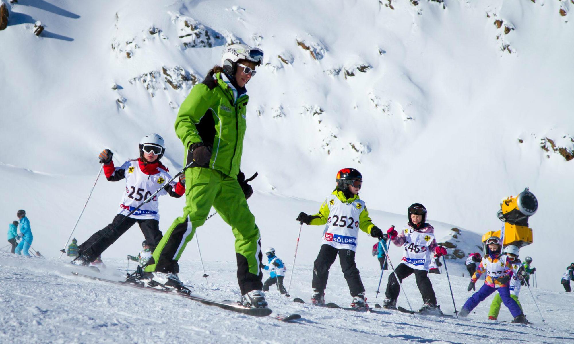 Ein Skilehrer bringt 5 Kindern das Skifahren auf einer Piste im Skigebiet Sölden bei.