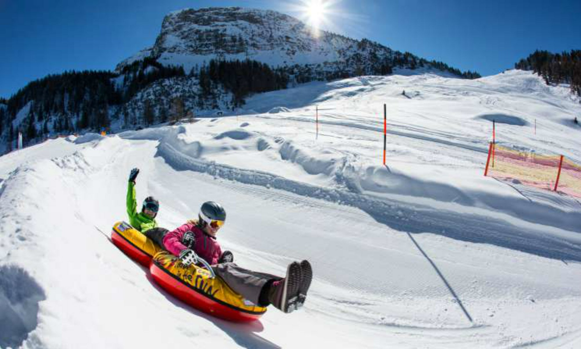 2 people snowtubing in the sunshine in the Zillertal Arena.
