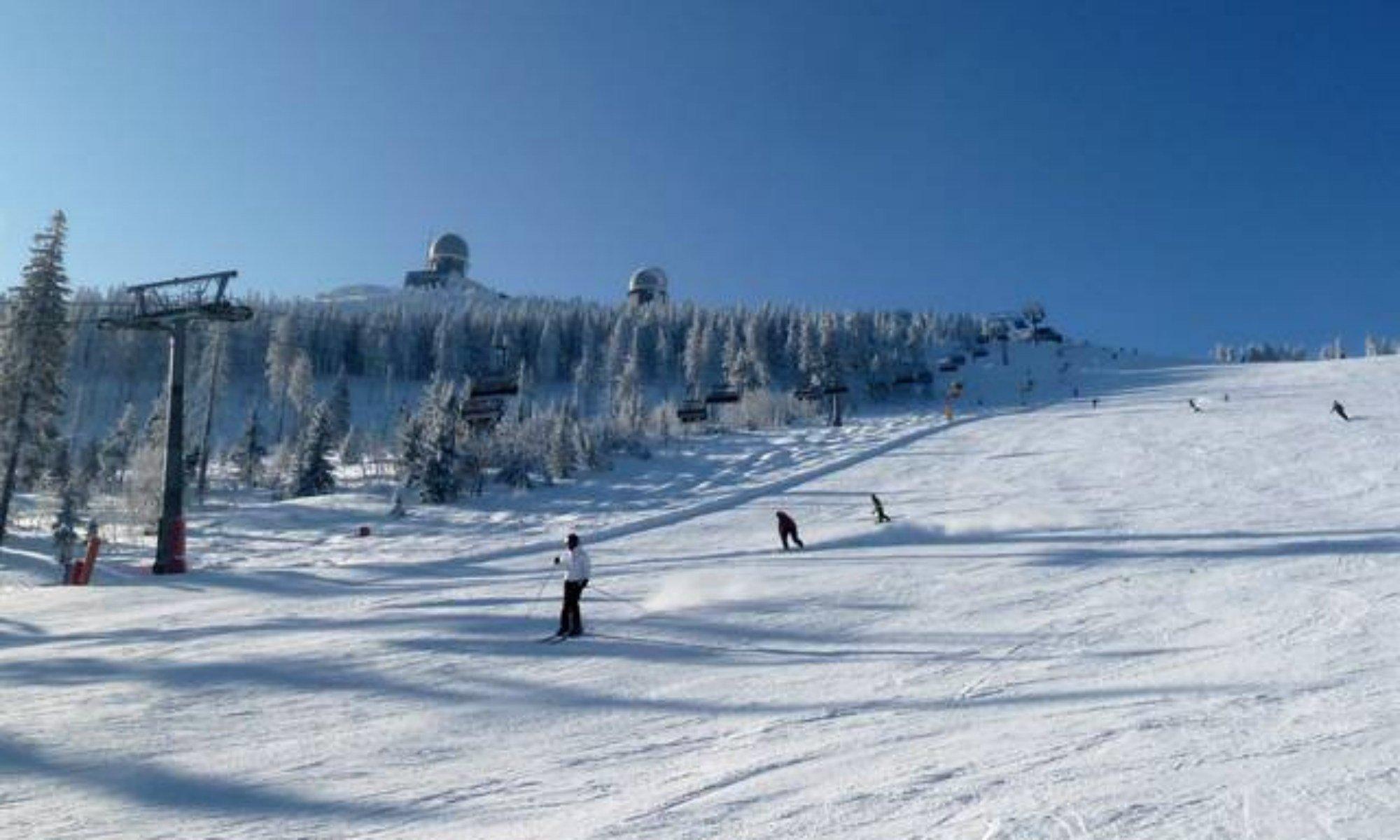 Skipiste bei Sonnenschein mit verschneiten Wald im Hintergrund am Großen Arber.