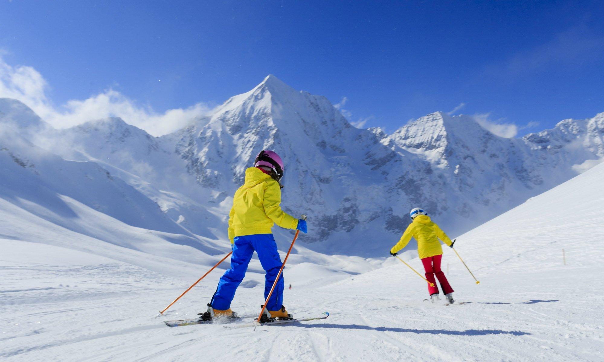 Zwei Skifahrer auf einer Piste in den Bergen.