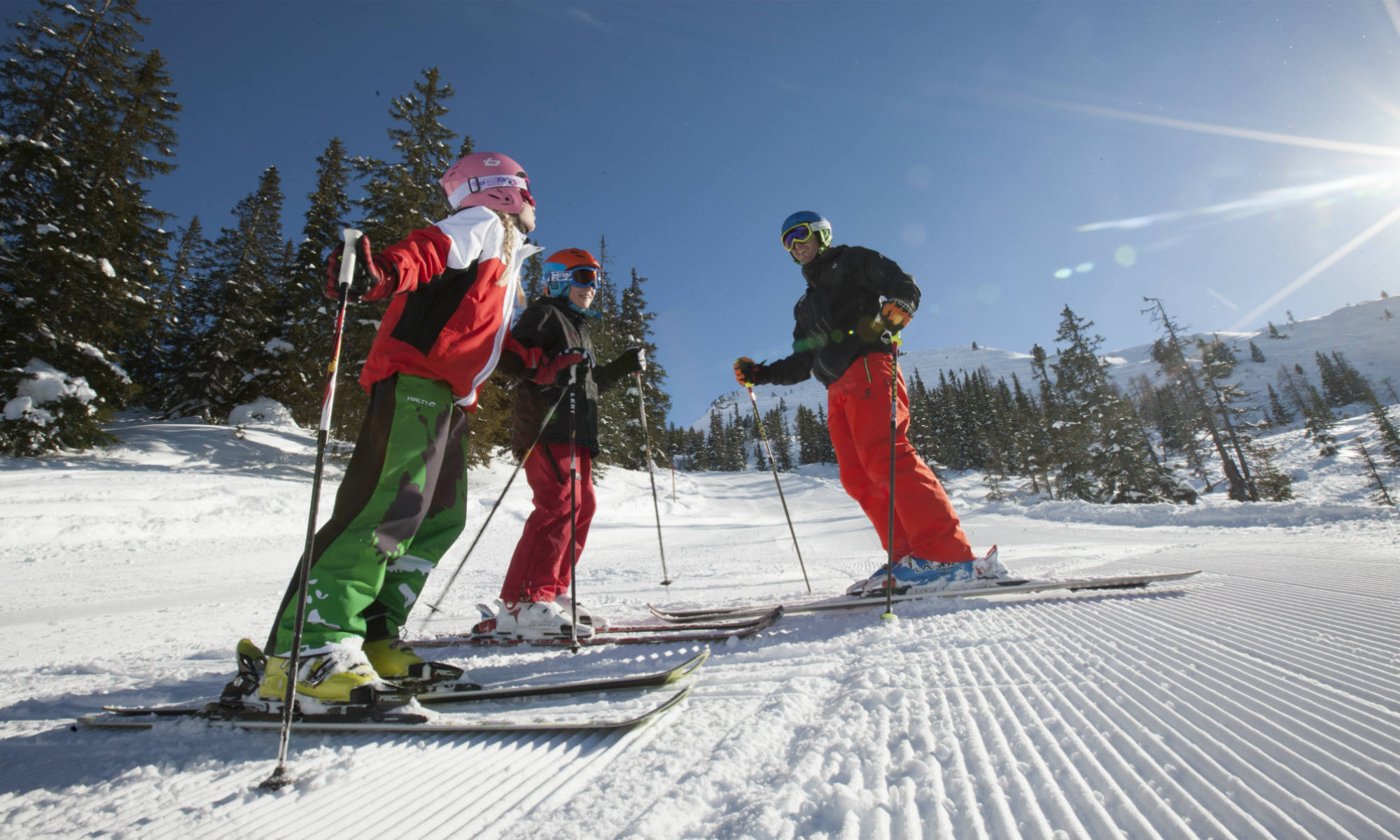 Two children and their private instructor on a sunny slope.