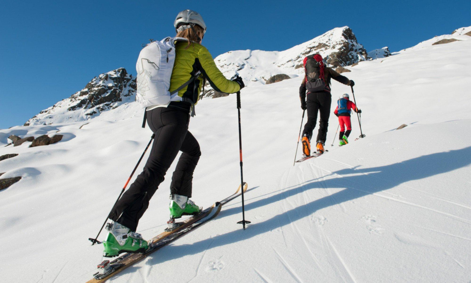 Tre persone fanno un giro sciistico e salgono sulla montagna.