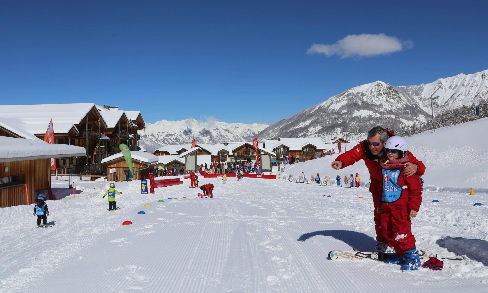 Kinder lernen das Skifahren mit Hilfe von kindgerechten Übungsutensilien in Les Orres.