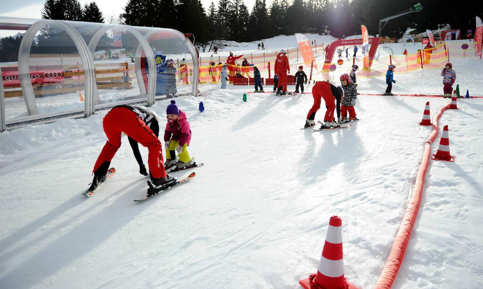 Kinder üben das Skifahren mit lustigen Spielen im Kinderland in Oberstdorf.