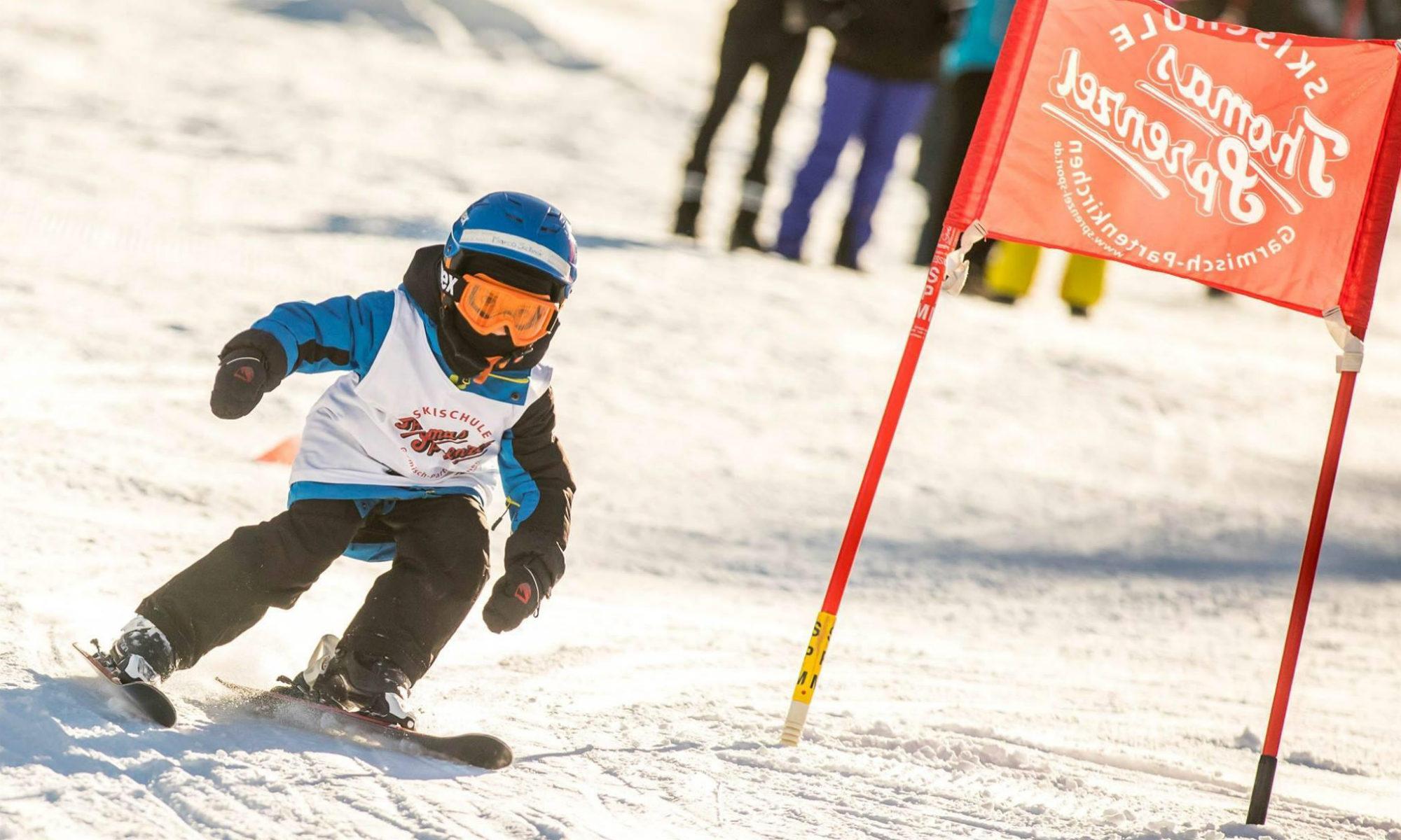 Ein Skianfänger umfährt ein Hindernis und übt das Steuern der Skier im Kinderland in Garmisch-Partenkirchen.