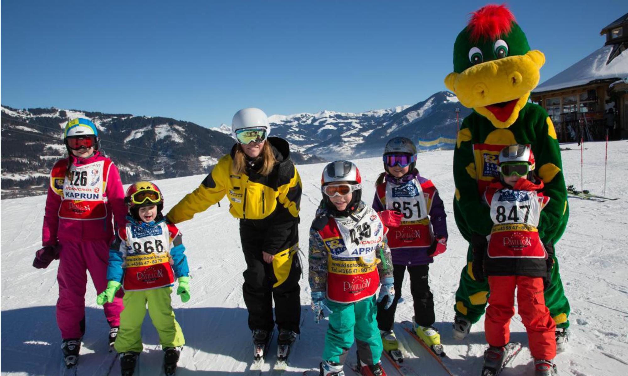 Skianfänger haben Spaß mit dem Maskottchen des Kinderlandes in Kaprun.