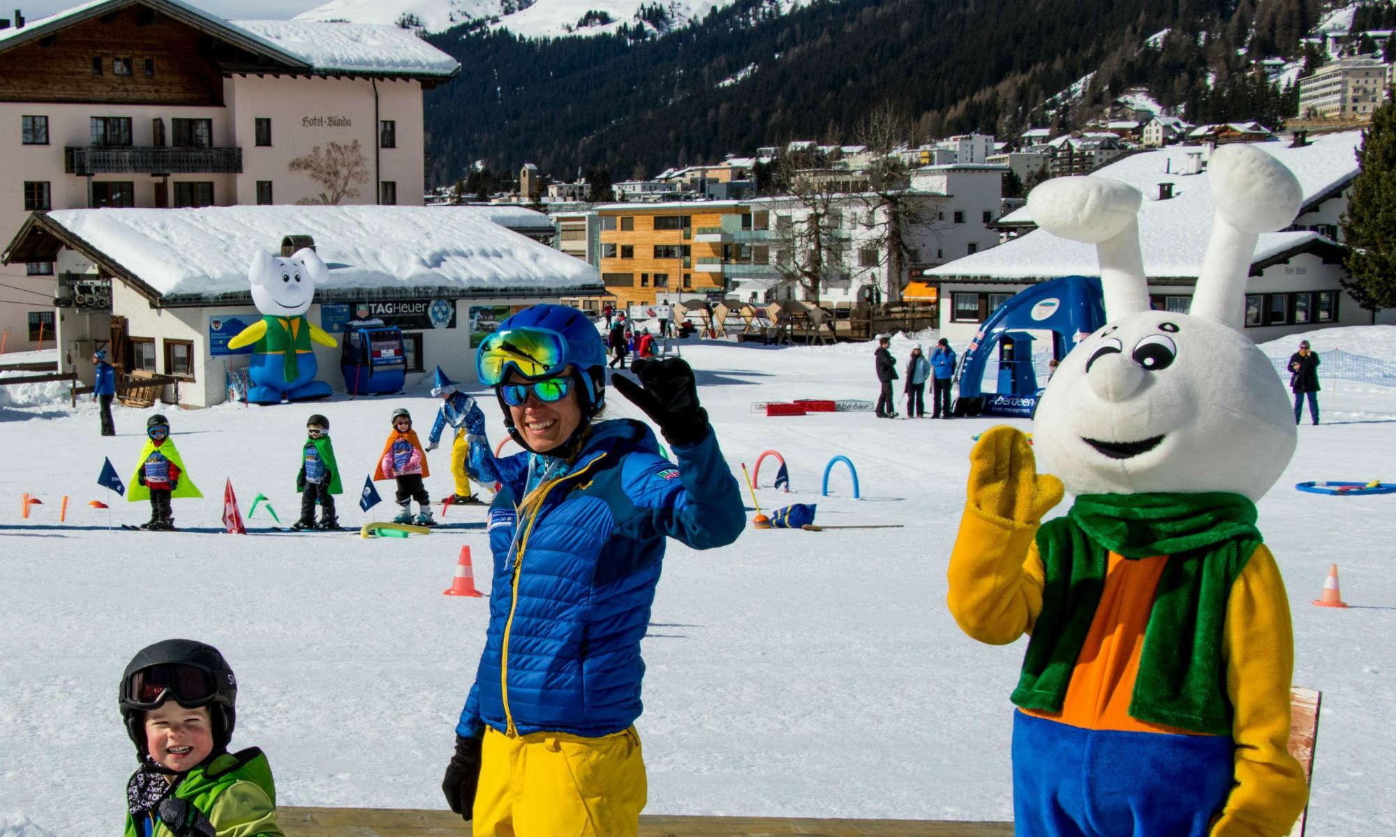 Das Maskottchen Snowli, ein Skilehrer und ein Kind lachen und winken im Kinderland.