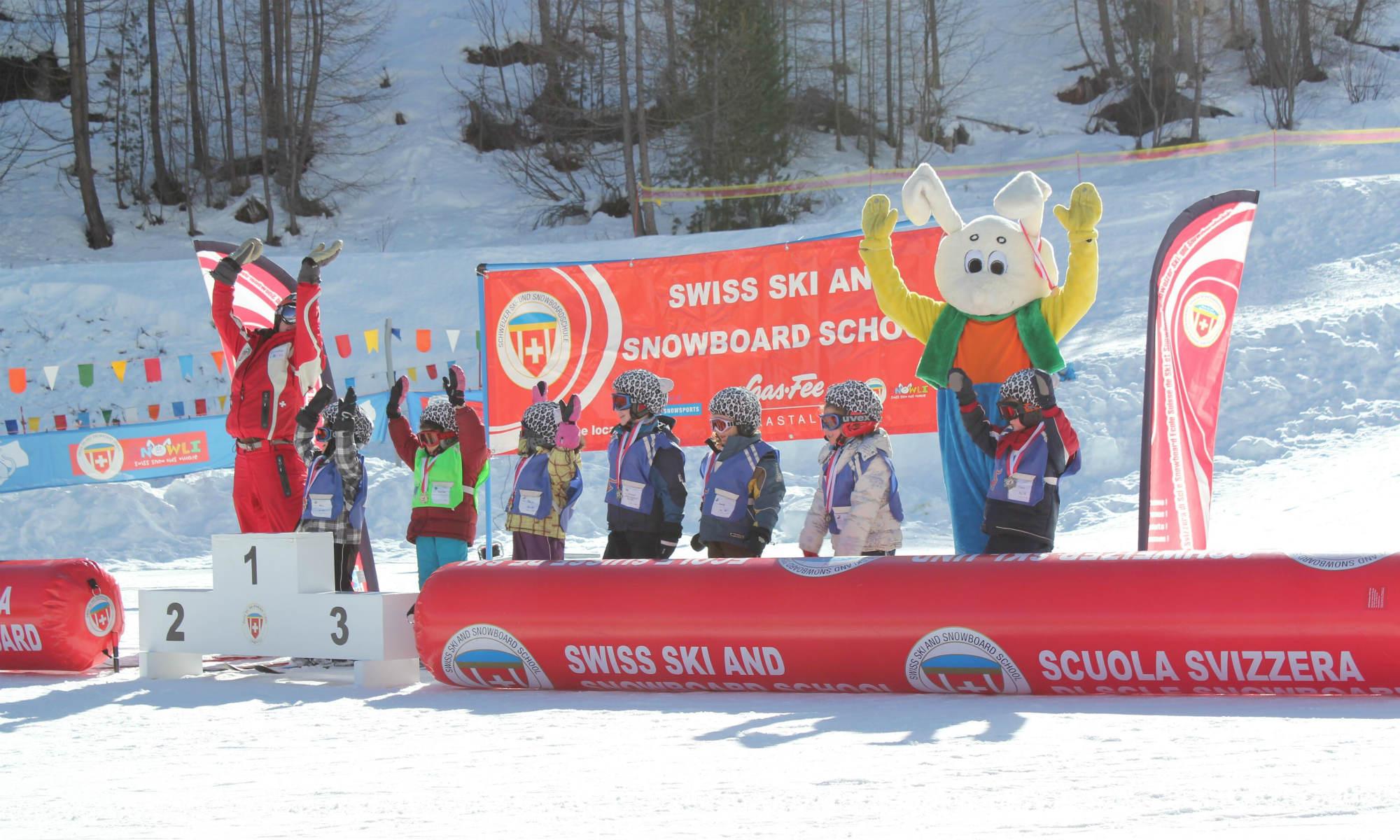 Eine Gruppe Kinder feiert bei der Siegerehrung am Ende des Skikurses mit dem Maskottchen Snowli.