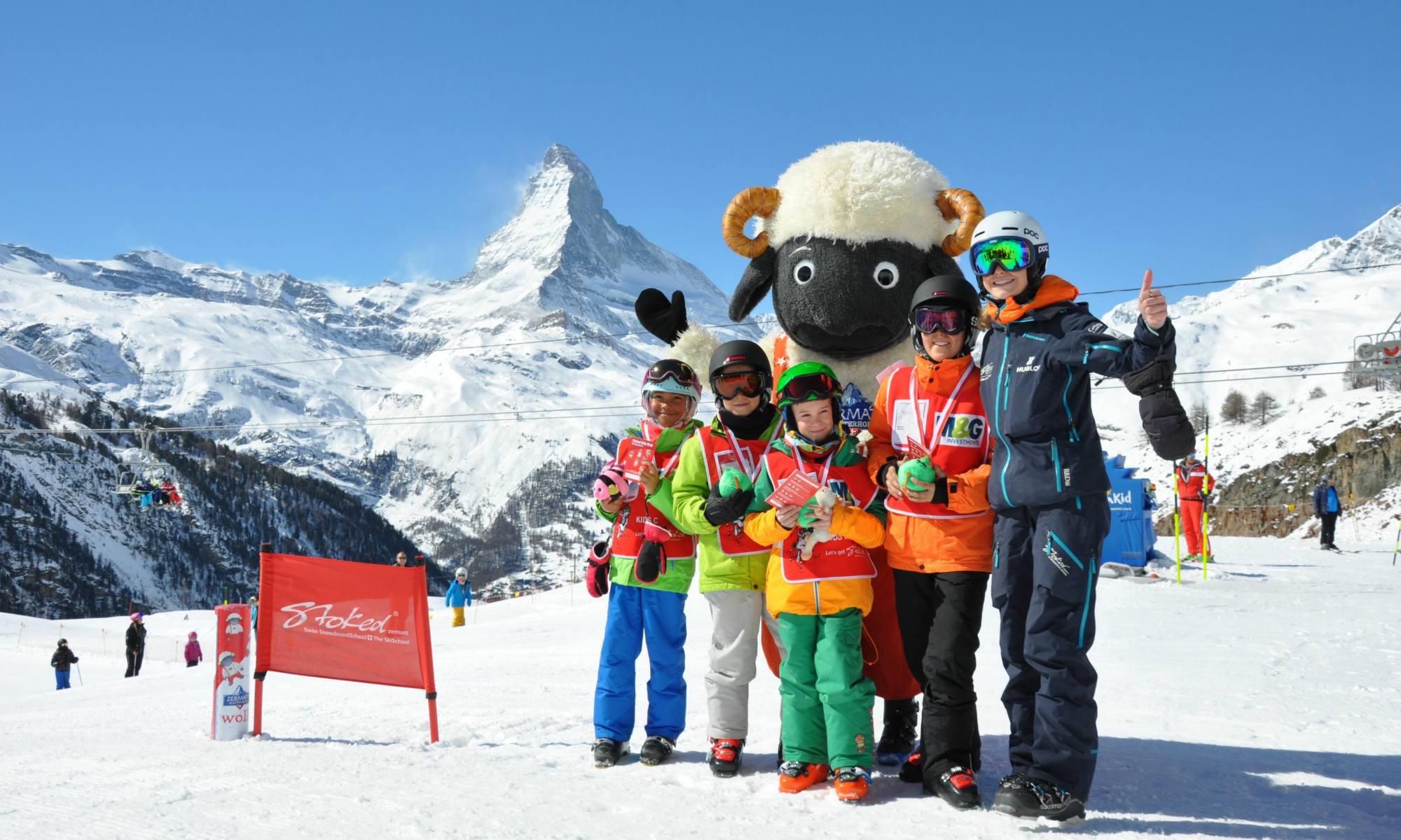 Eine Gruppe Kinder und eine Skilehrerin stehen auf einer Skipiste vor dem Panorama des Matterhorns.