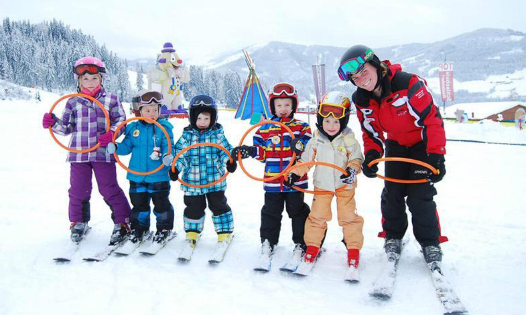 Eine Gruppe Skianfänger übt das Steuern der Skier im Kinderland in Westendorf.
