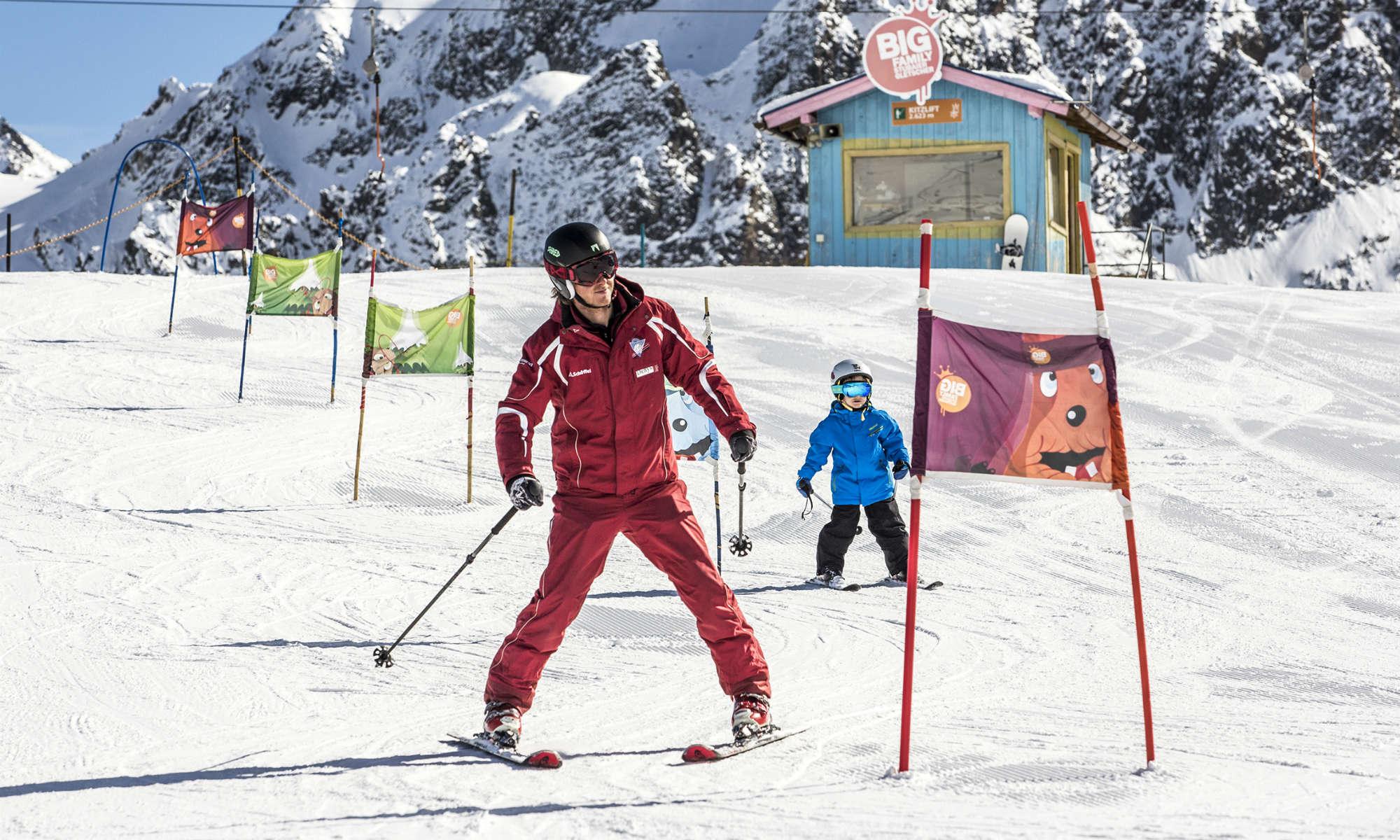 Ein Skilehrer zeigt einem Kind, wie man die Slalompiste am Stubaier Gletscher am besten bewältigt.