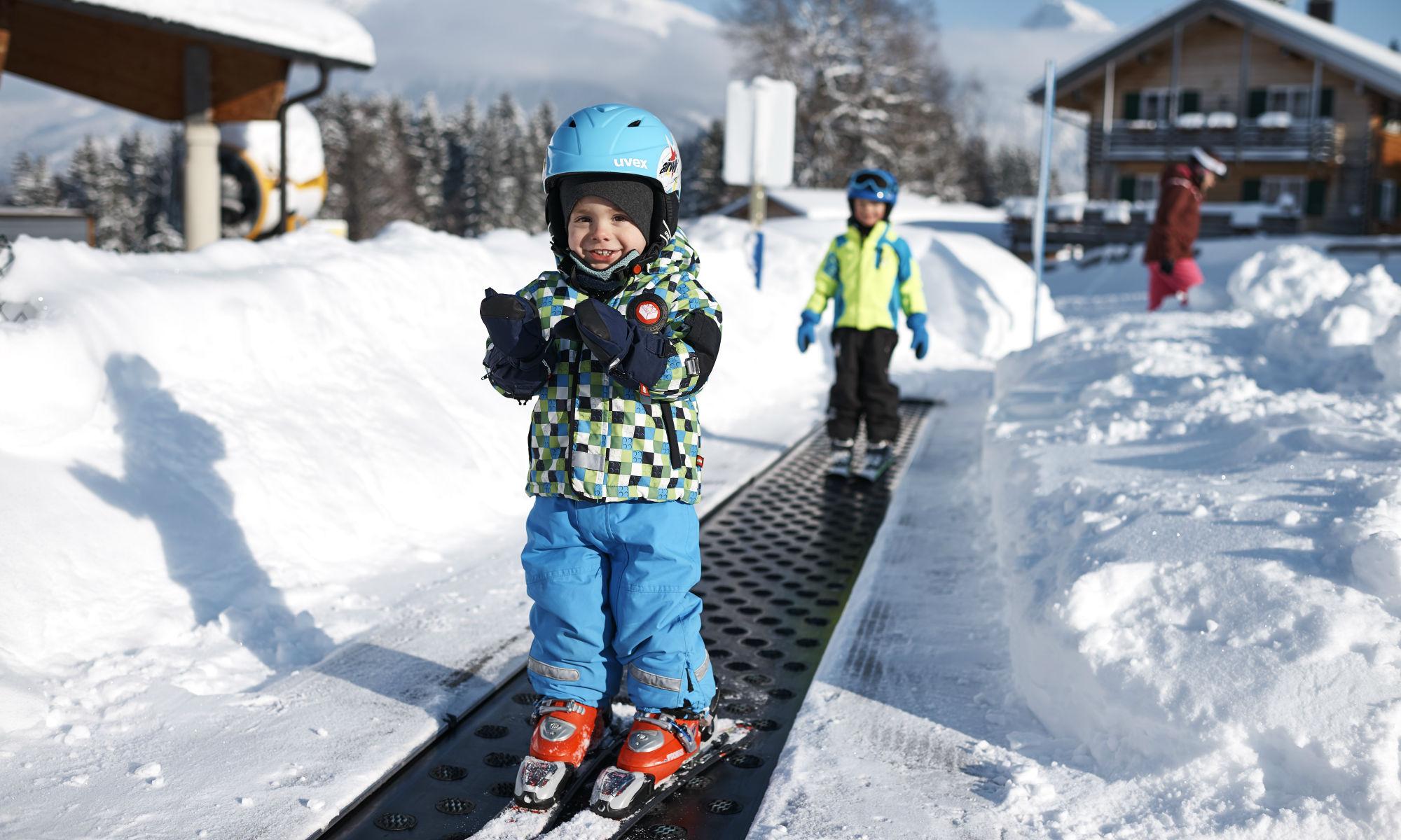 Zwei Kinder fahren mit einem Zauberteppich im Skigebiet Oberstdorf.
