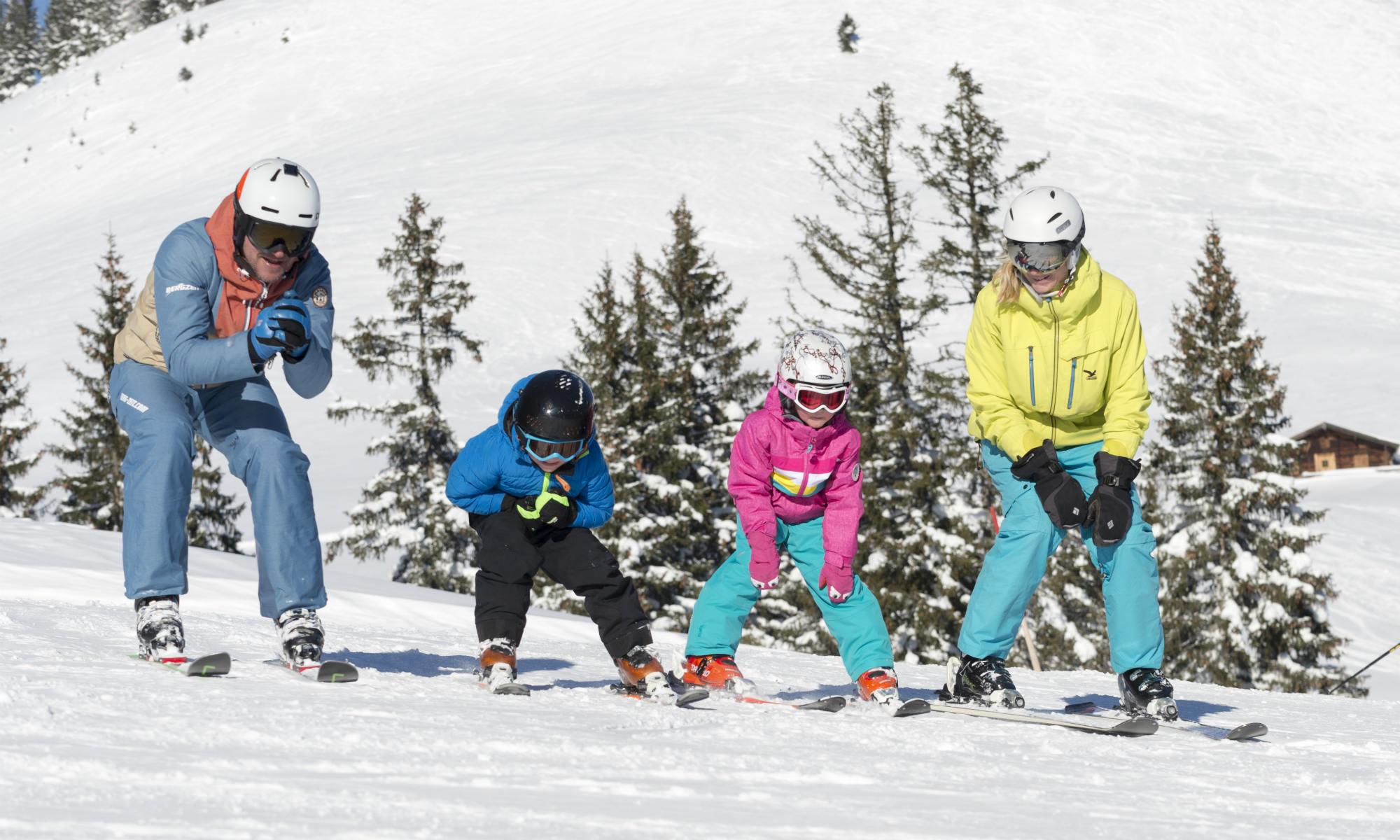 Familie mit 2 Kindern beim Üben der Skitechnik auf einer Piste in Lofer.