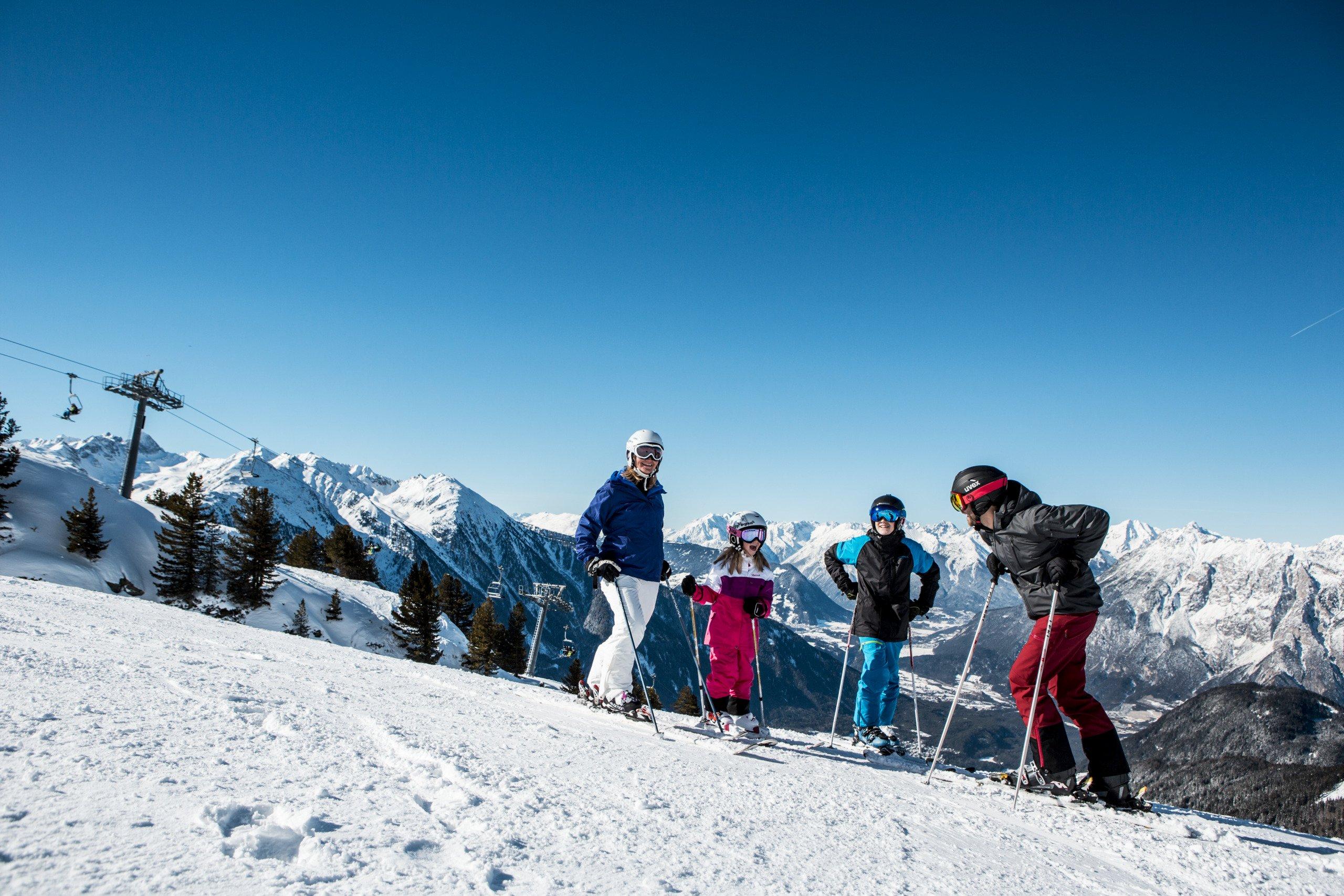 Eine Familie beim Skifahren auf einer sonnigen Piste im Skigebiet Oetz-Hochoetz.