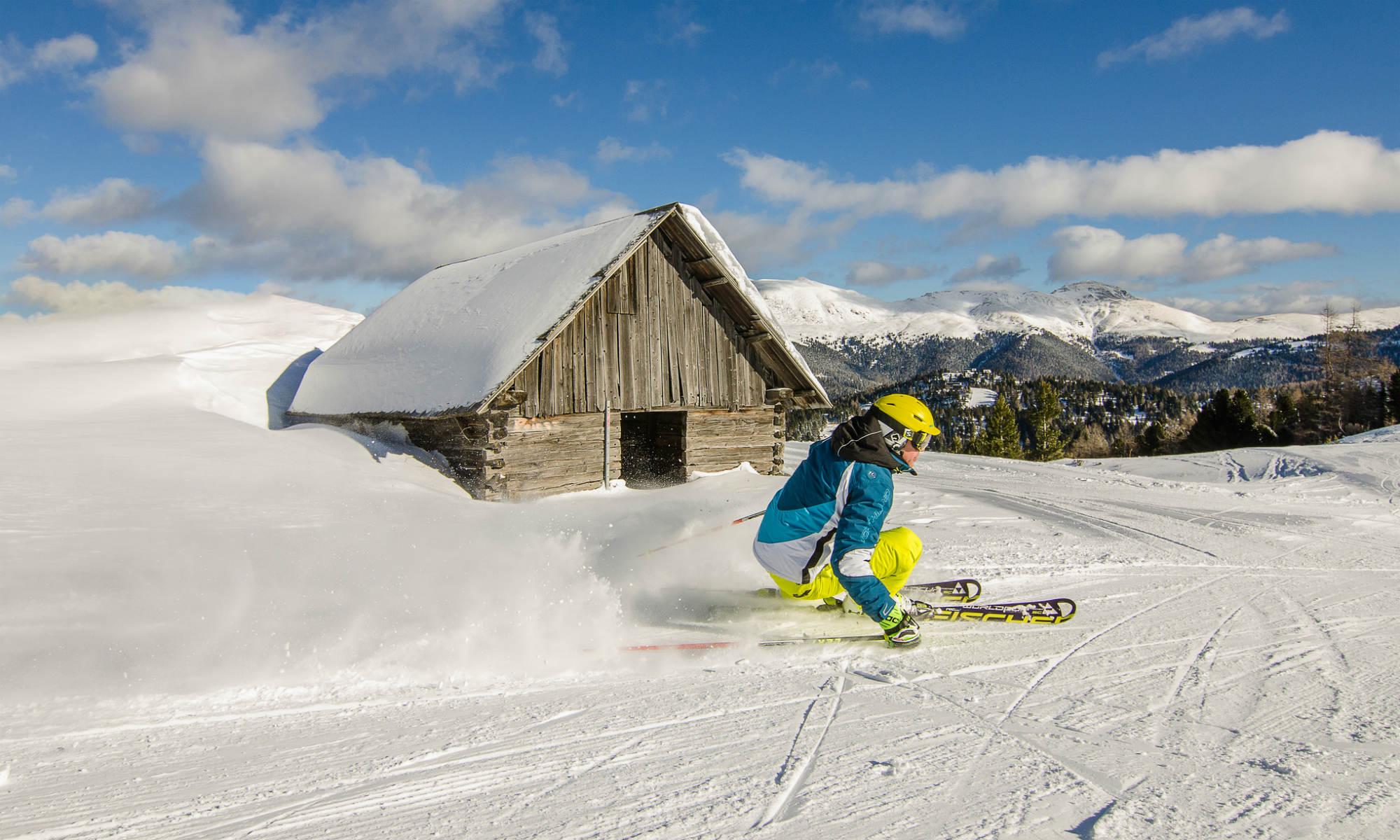 Ein Skifahrer beim Carven auf einer sonnigen Piste auf der Turracher Höhe.