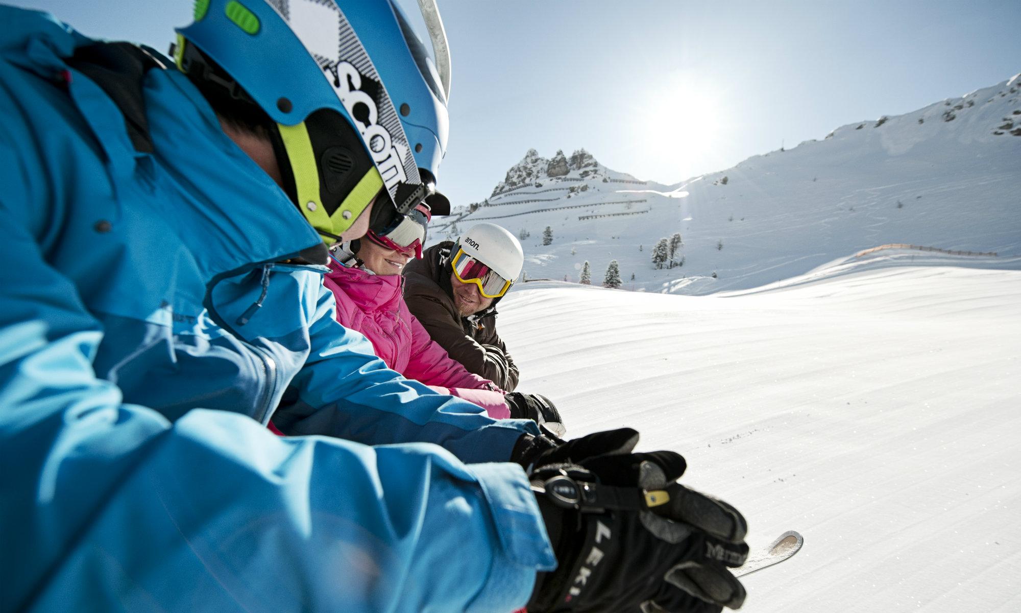 Drei Skifahrer sitzen auf einem Sessellift und unterhalten sich.