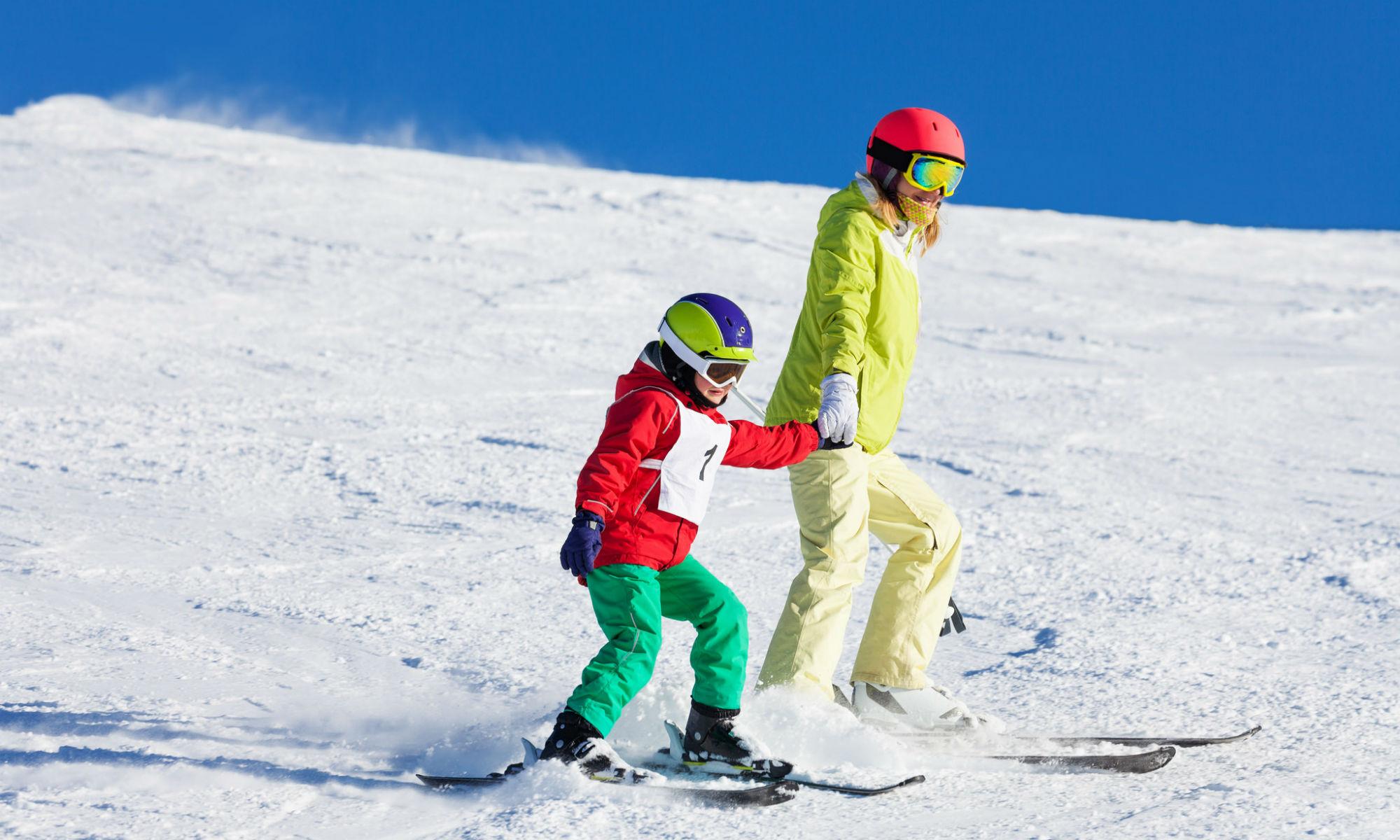 Ein Kind fährt mit seiner Mutter Hand in Hand die Skipiste hinunter.