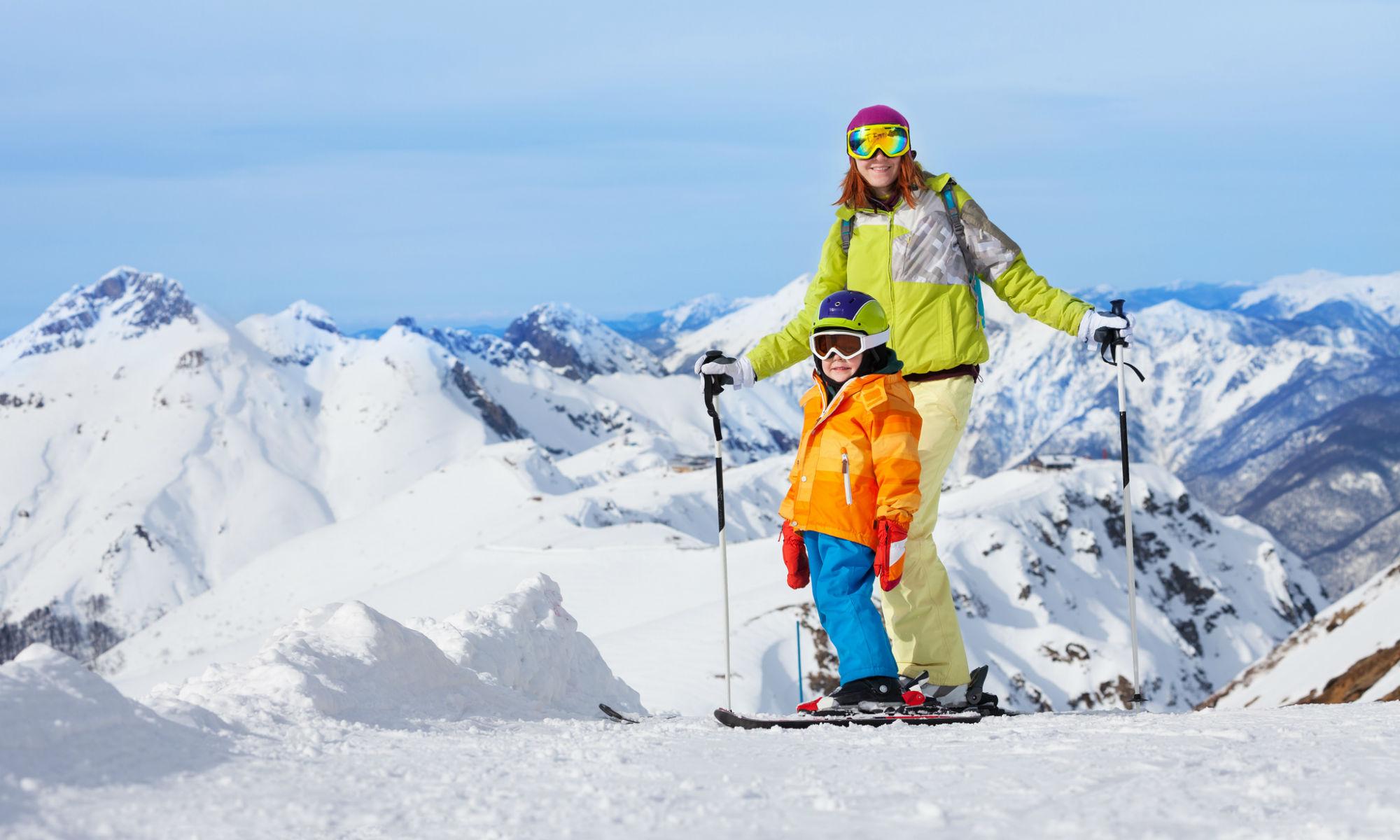 Mutter und Kind posieren mit Skiern vor einer Bergkulisse.