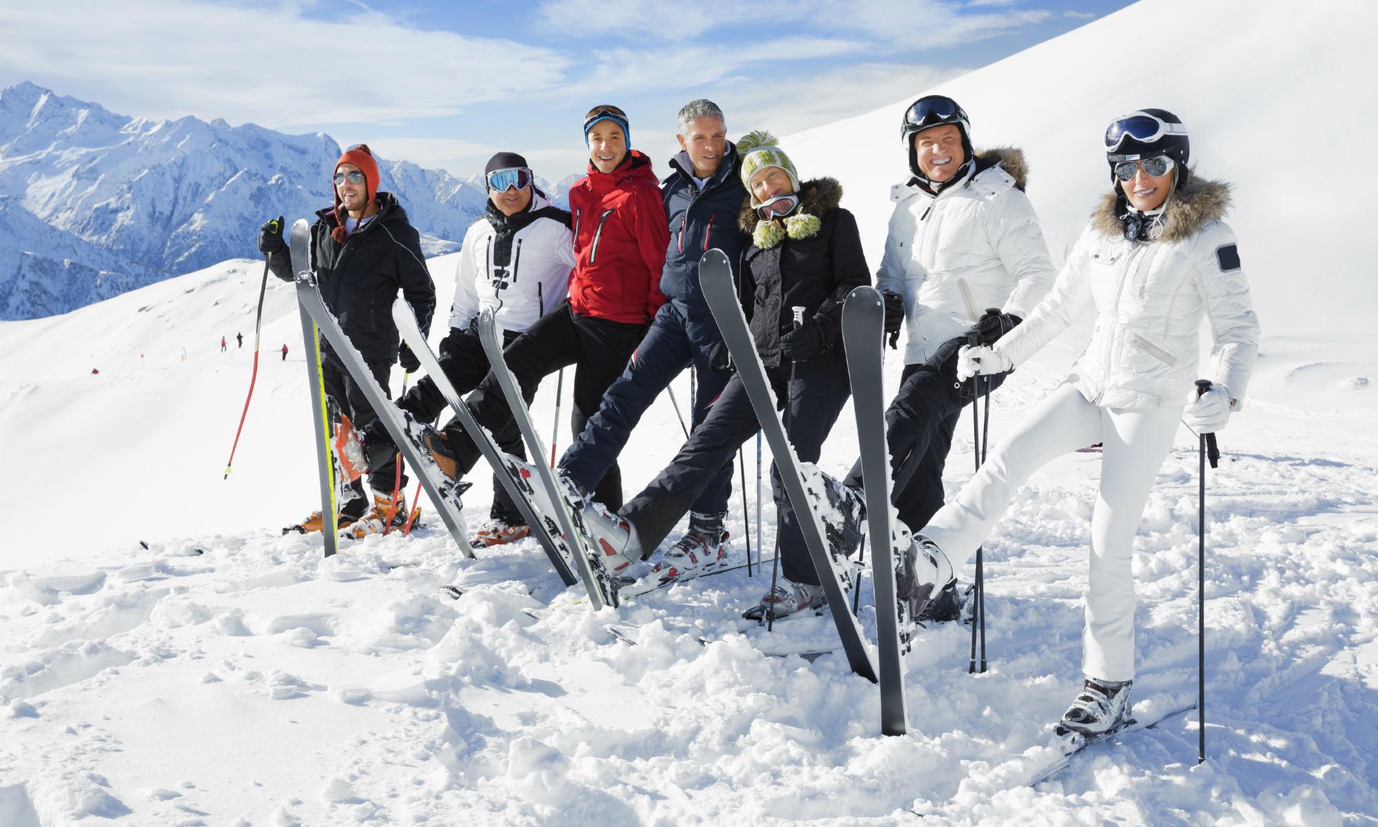 7 Skifahrer mit guter Laune auf der sonnigen Piste.