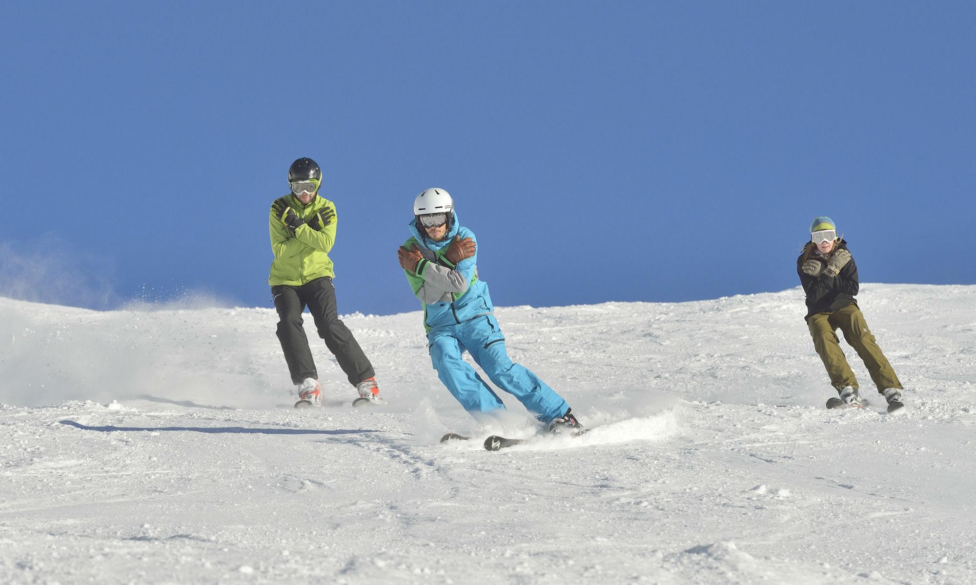 Privater Skilehrer mit 2 fortgeschrittenen Skifahrern beim Üben auf der sonnigen Piste.