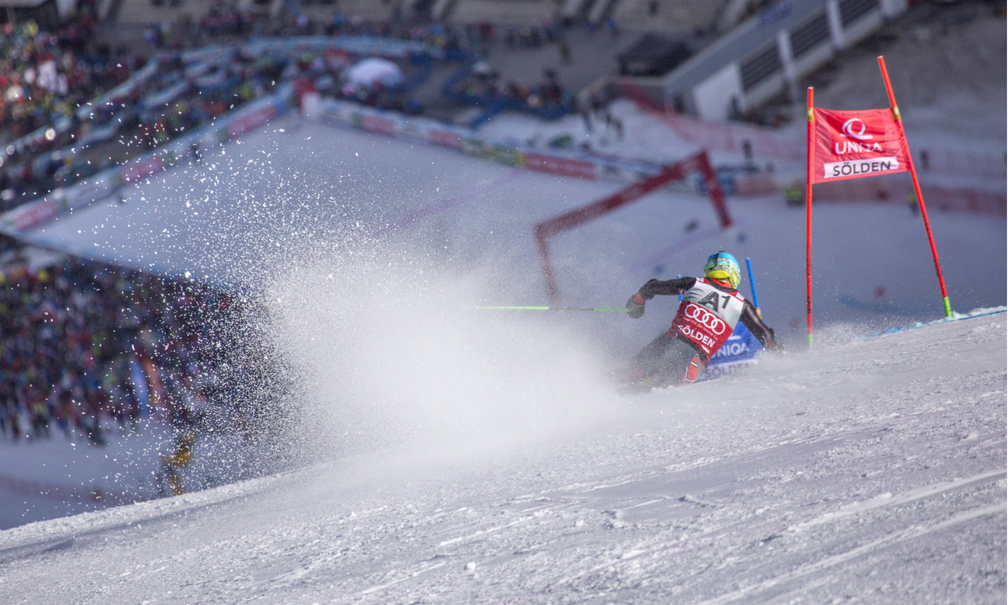 An alpine skier skiing down a slalom slope.